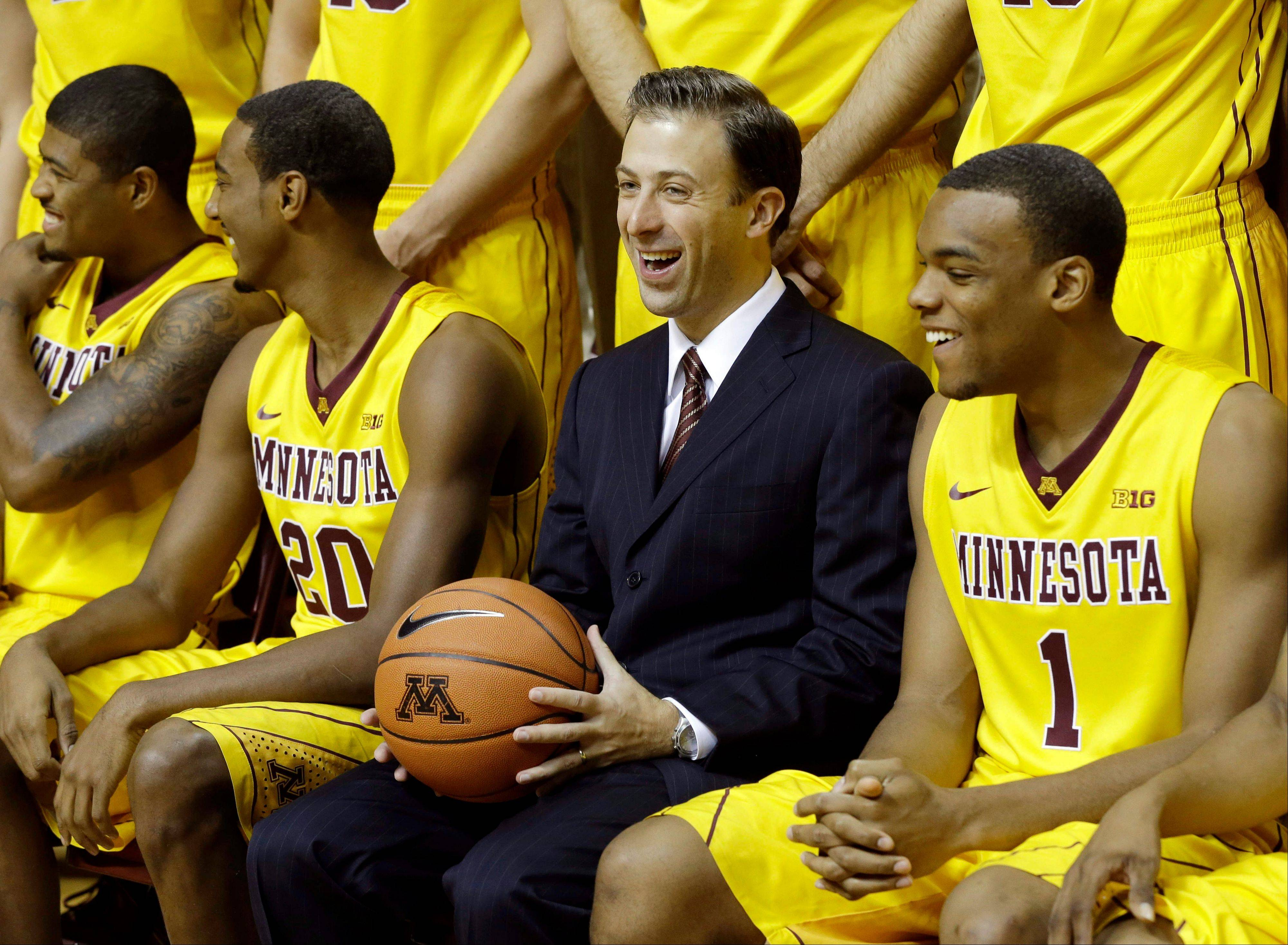 New Minnesota men's basketball coach Richard Pitino enjoys a laugh along with, from left, Maverick Ahanmisi, Austin Hollins and Andre Hollins during the setup for the formal team portrait Monday in Minneapolis.