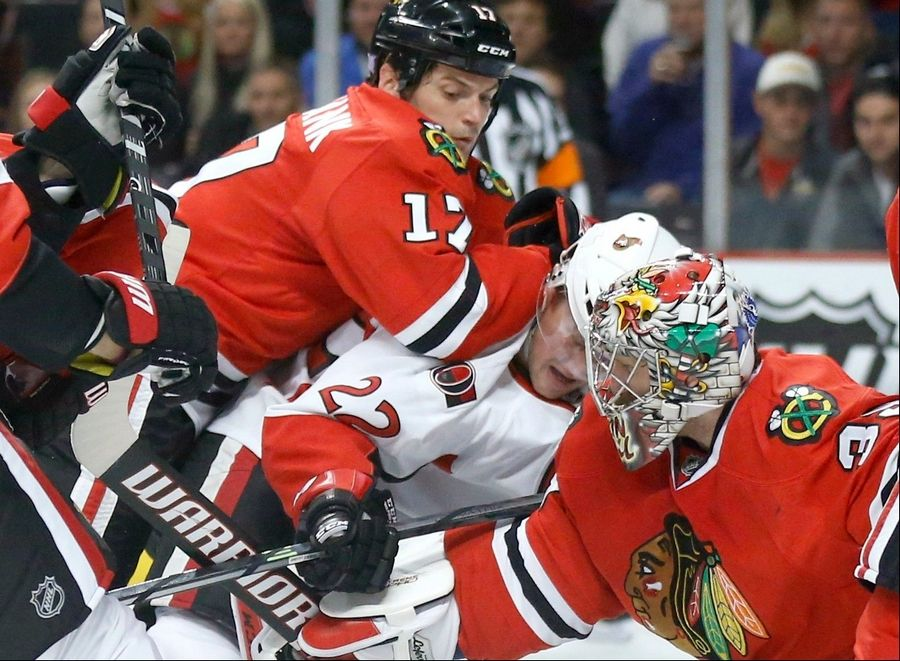 Ottawa Senators right wing Erik Condra (22) is sandwiched between Blackhawks defenseman Sheldon Brookbank (17) and goalie Nikolai Khabibulin during the first period of an NHL hockey game Tuesday, Oct. 29, 2013, in Chicago.