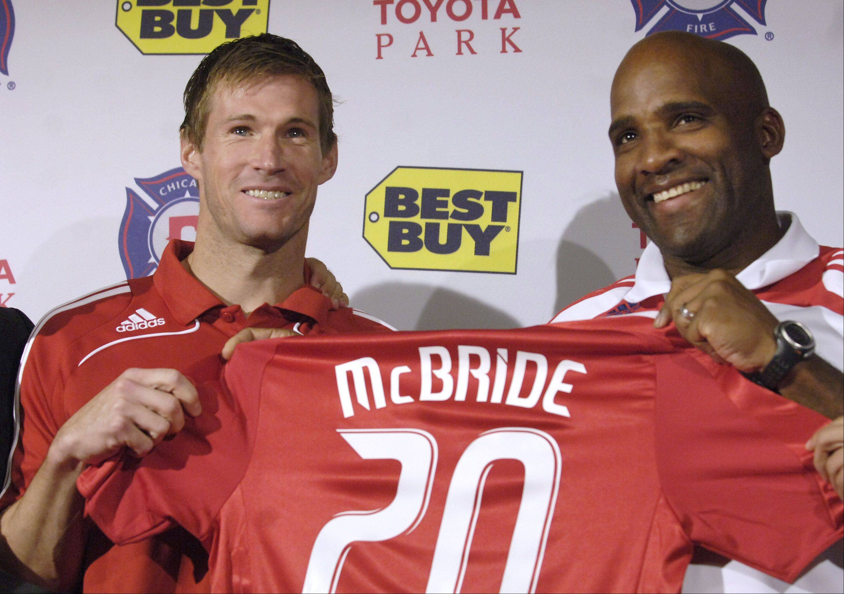 Brian McBride, left, receives a new jersey from head coach Denis Hamlett during a Chicago Fire press conference at Toyota Park in Bridgeview.