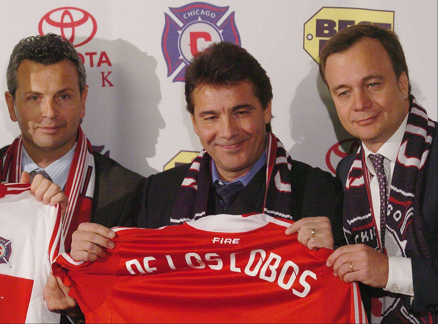 Bob Chwedyk/bchwedyk@dailyherald.com � From left, Technical Director Frank Klopas, new Chicago Fire coach Carlos de los Cobos and Managing Director Javier Leon hold up the coach's new jersey during news conference at Toyota Park.