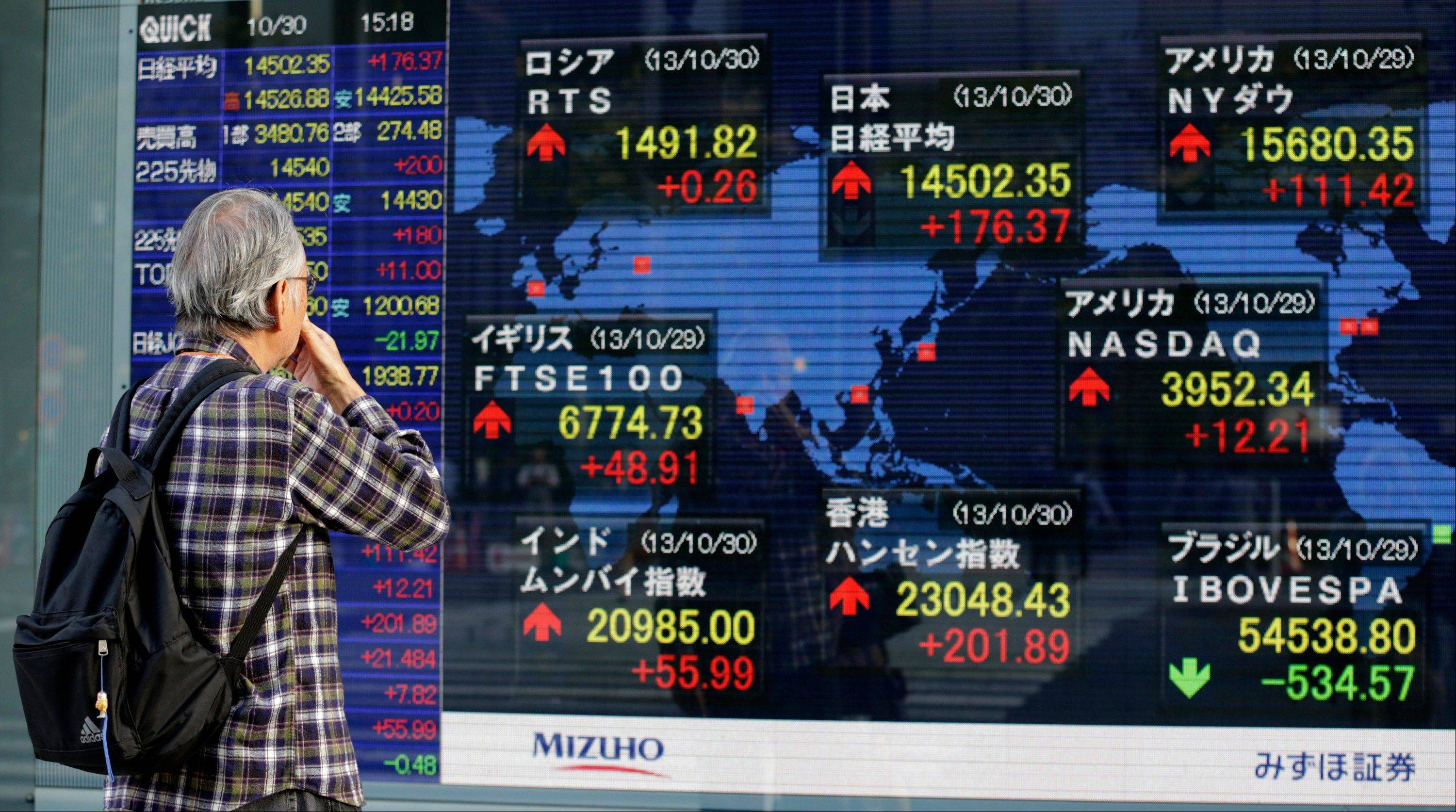 A man watches an electronic stock indicator in Tokyo.