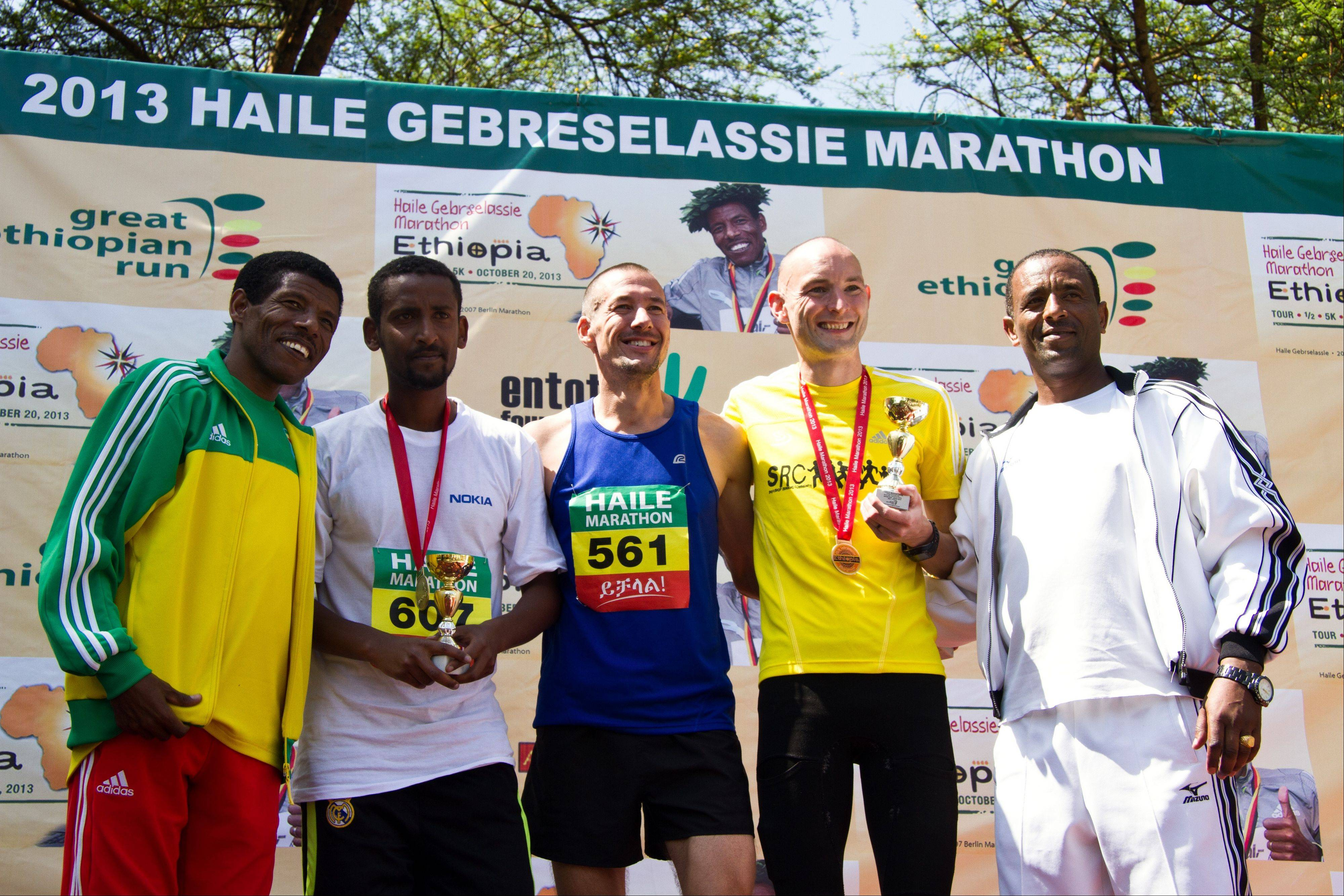 Jason Dolan, center, of Inverness, poses for photos after winning first place in the 2013 Haile Gebreselassie Marathon Oct. 20 in southern Ethiopia. The marathon had two divisions: one for elite Ethiopian runners, and one for foreign runners called the International Mass Marathon. Dolan won in the latter division. Pictured from left to right are race namesake Gebrselassie, third place finisher Esayas Yayneshet, Dolan, second place winner Simon Newton from Great Britain, and Ethiopian marathoner Belay Welasha. Not pictured is Megan McClowry, of Naperville, who won the marathon�s women�s division.