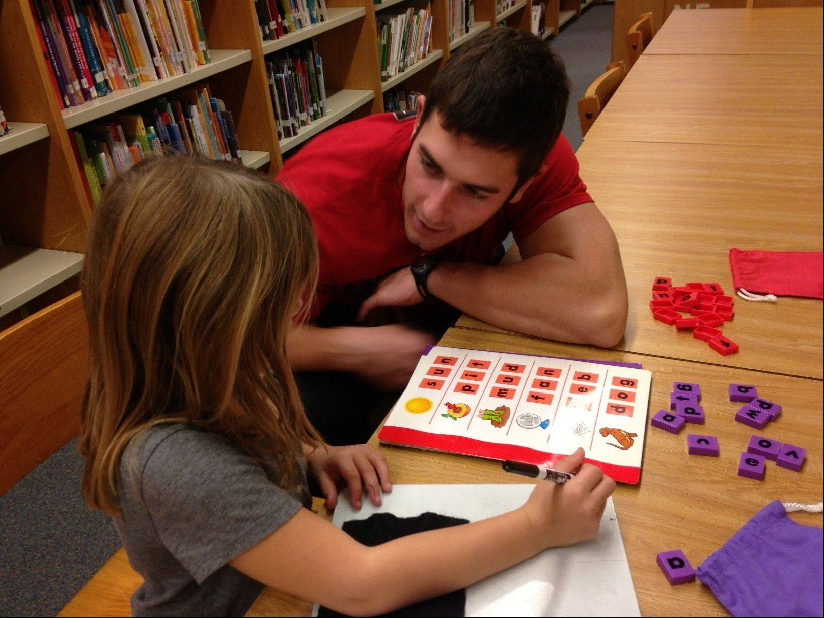 "David Martin, a physical education student teacher at Kaneland John Stewart Elementary School in Elburn, works with a kindergartner on a ""building words"" exercise during a time when all students in the building concentrate on reading and writing. Such exercises helped the school make significant progress on standardized testing."