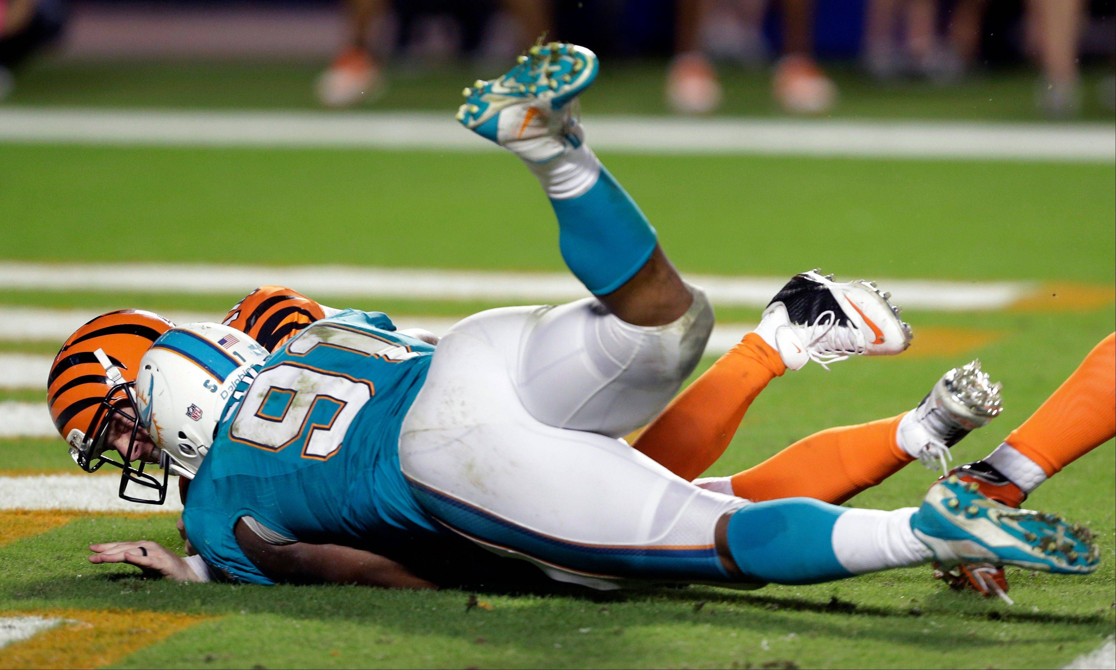 Miami Dolphins defensive end Cameron Wake sacks Cincinnati Bengals quarterback Andy Dalton in the end zone for a safety during overtime Thursday night.
