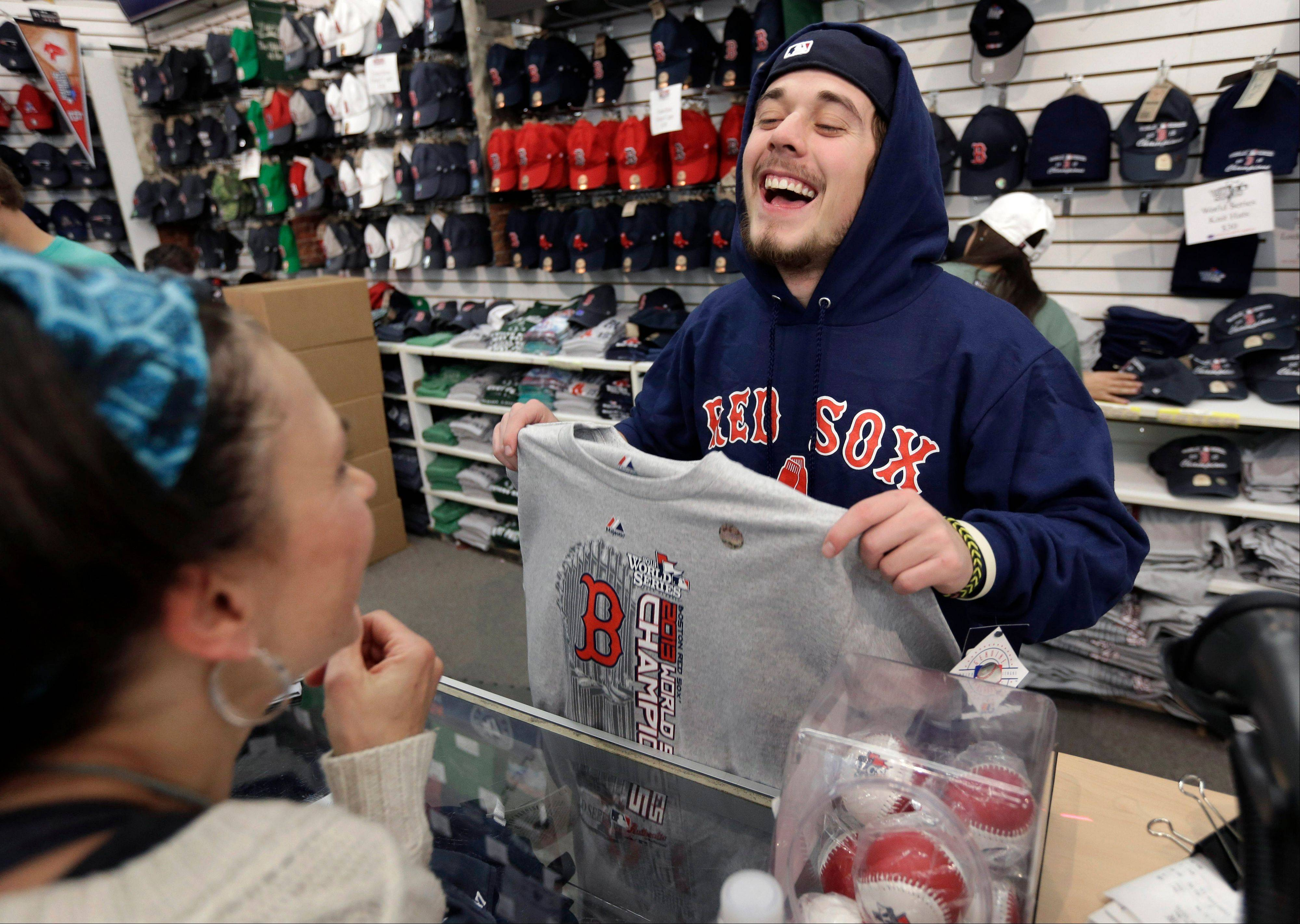 Worker Jake Miskin of Boston, right, laughs with Lori Leduc, of Calgary, Alberta, Canada, as she buys a 2013 baseball World Series champions shirt at a shop near Fenway Park on Thursday.