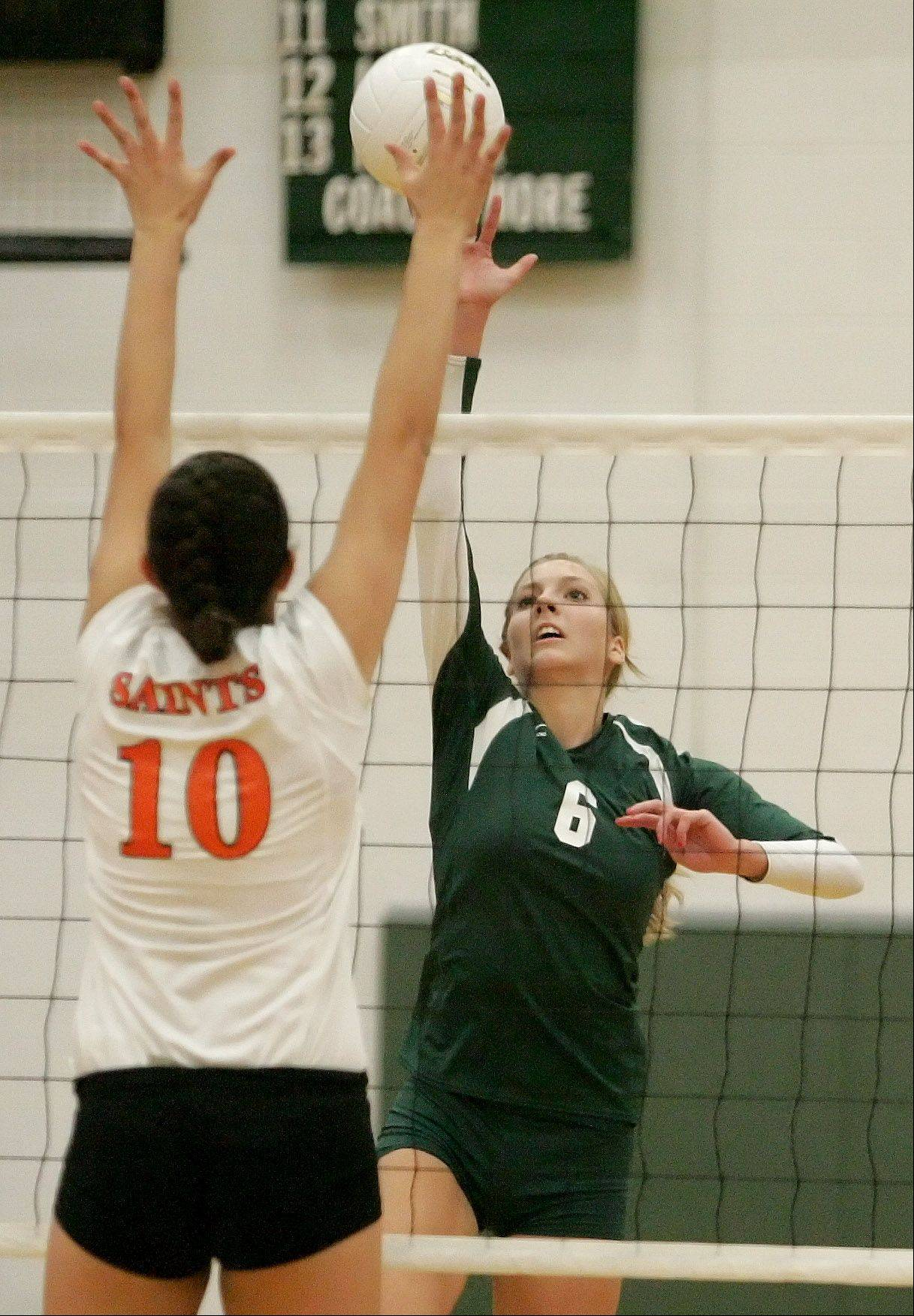 Rachel Minarick of Waubonsie Valley hits the ball over as Mikaela Mosquera of St. Charles East goes up to block in girls volleyball action on Monday in Aurora.