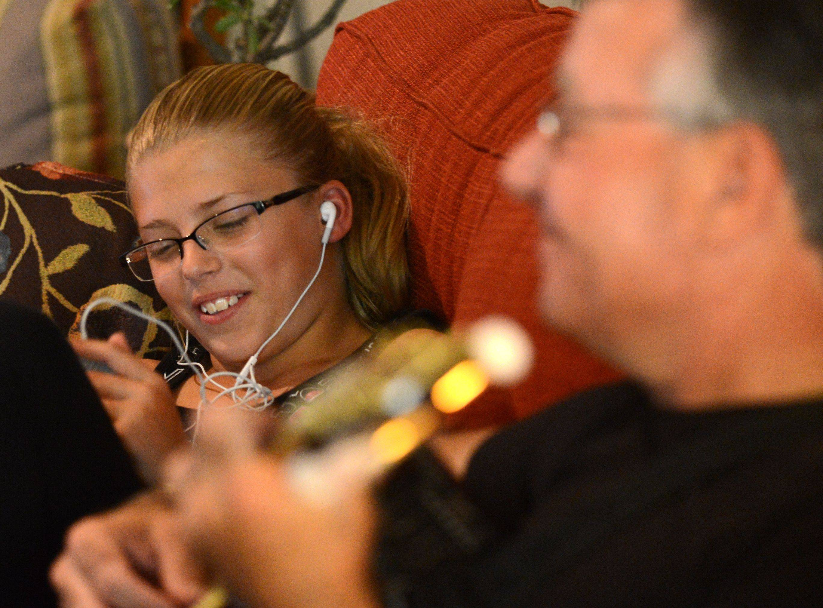 Michael McMein of East Dundee plays guitar while his granddaughter Olivia plays with her iPad at their home in East Dundee.