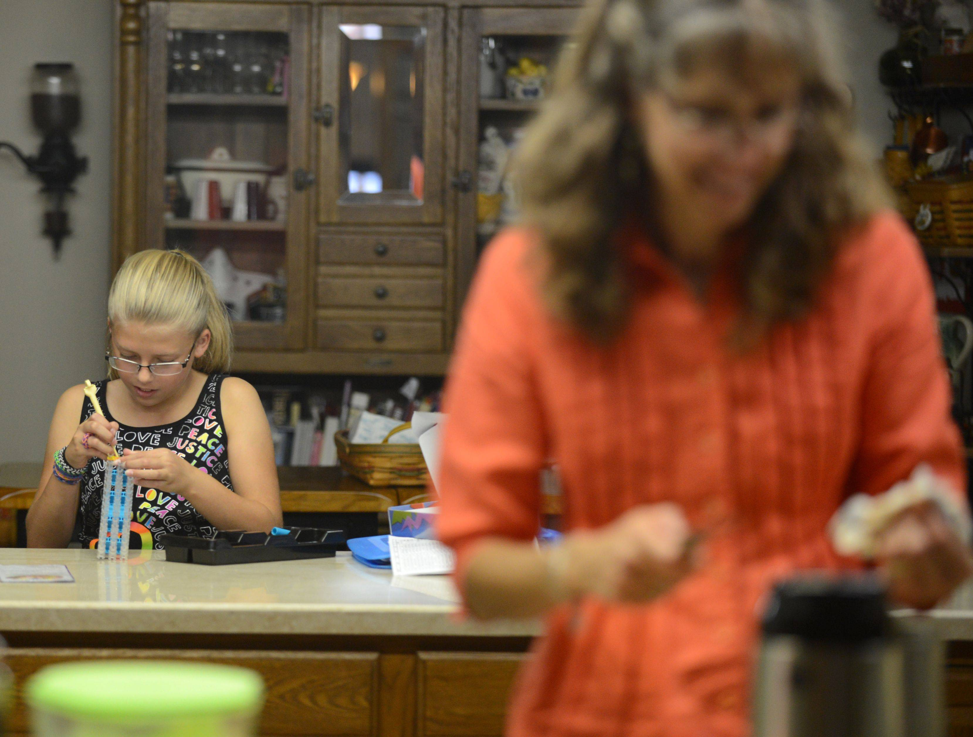 Olivia makes rubber band bracelets while her grandmother Kathy makes the next day's lunch at their home in East Dundee.