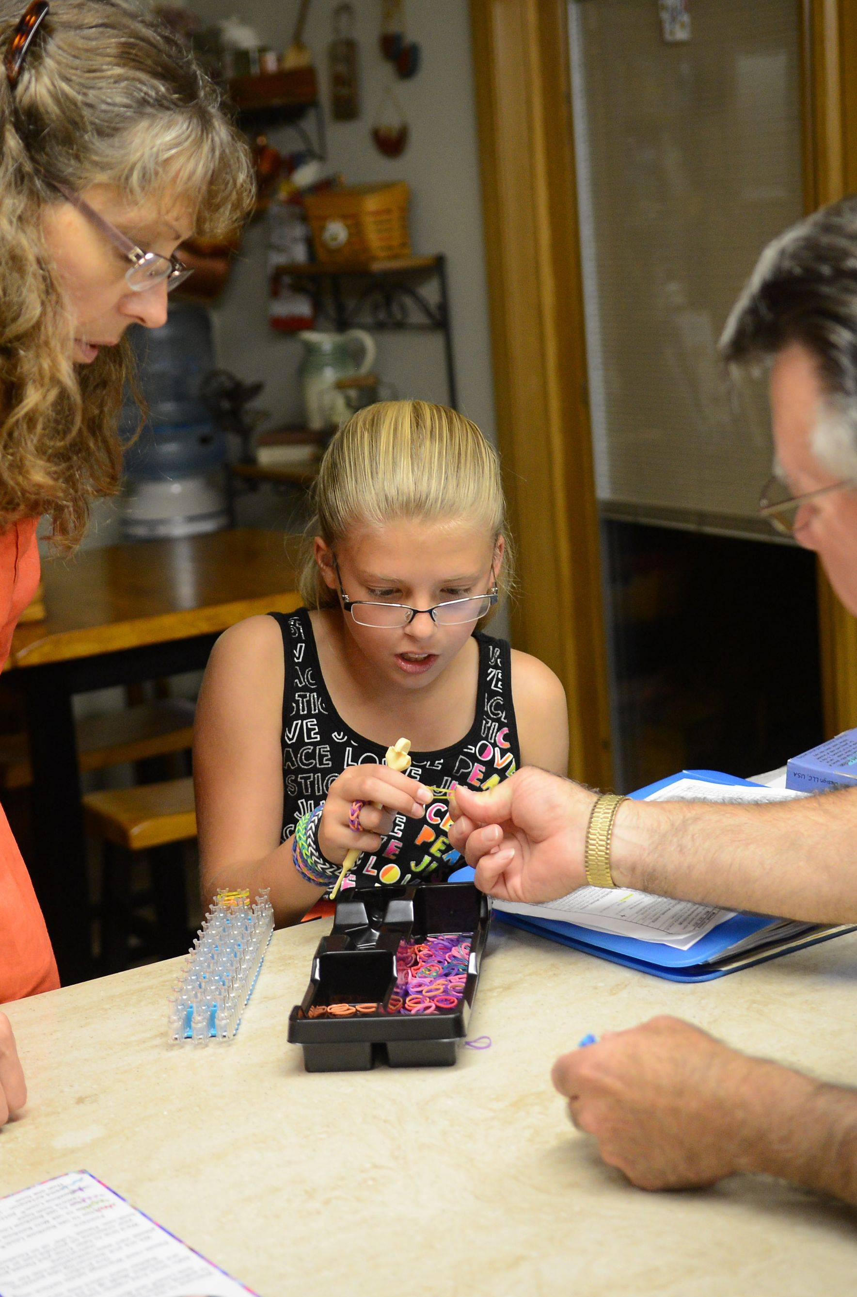 Olivia McMeins, center, makes rubber band bracelets with assistance from her grandparents, Michael and Kathy, at their home in East Dundee. The McMeinses have been raising their granddaughter since their daughter's death years ago when Olivia was very young.