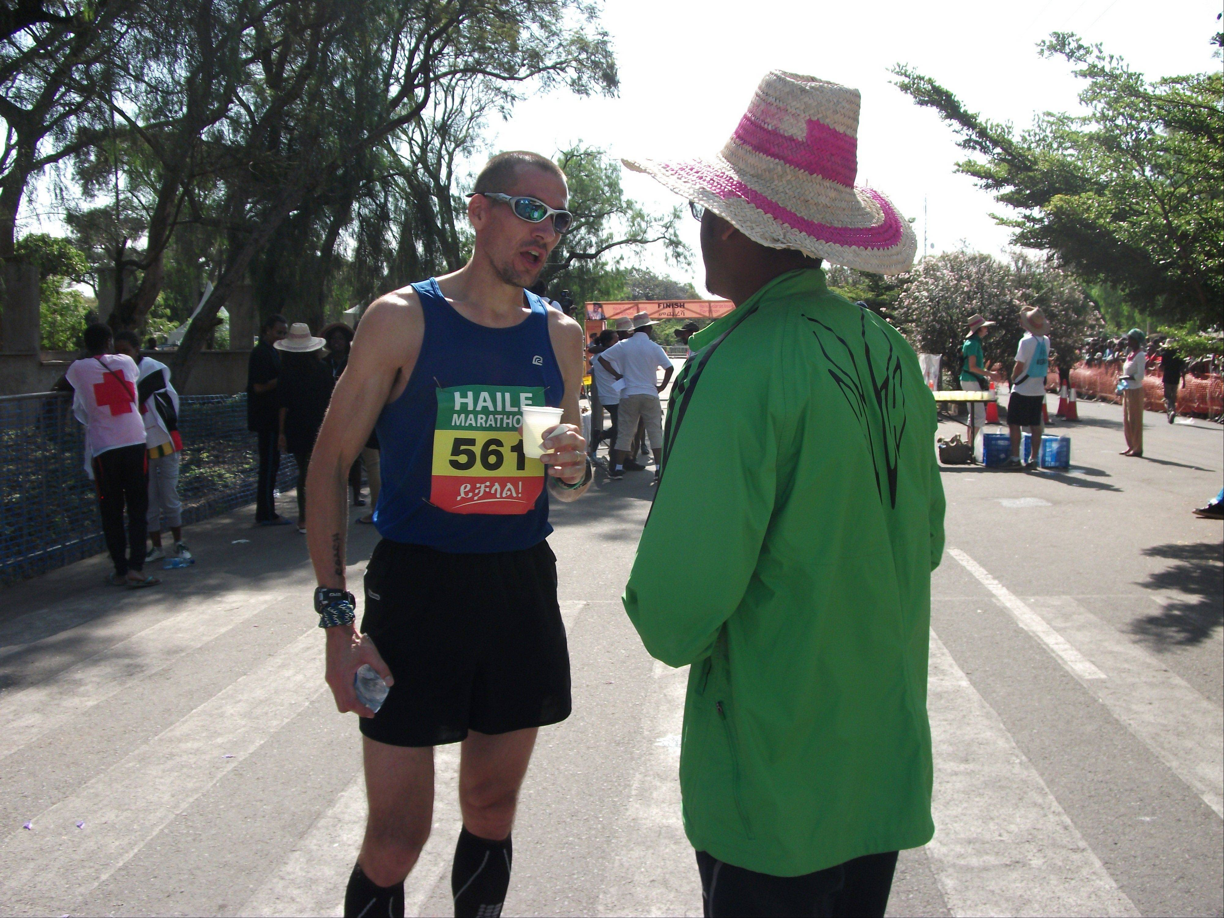 Jason Dolan, of Inverness, talks with a local man after winning the foreign runners category of the first 2013 Haile Gebrselassie Marathon in Hawassa, southern Ethiopia.