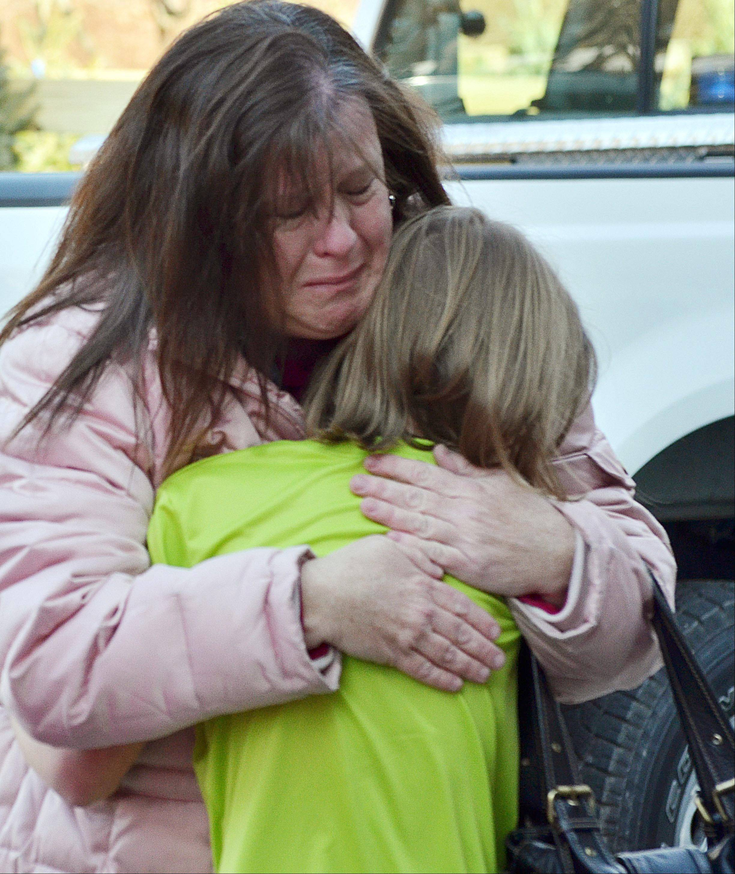 A mother hugs her daughter following a shooting at the Sandy Hook Elementary School in Newtown, Conn., Dec. 14, 2012.