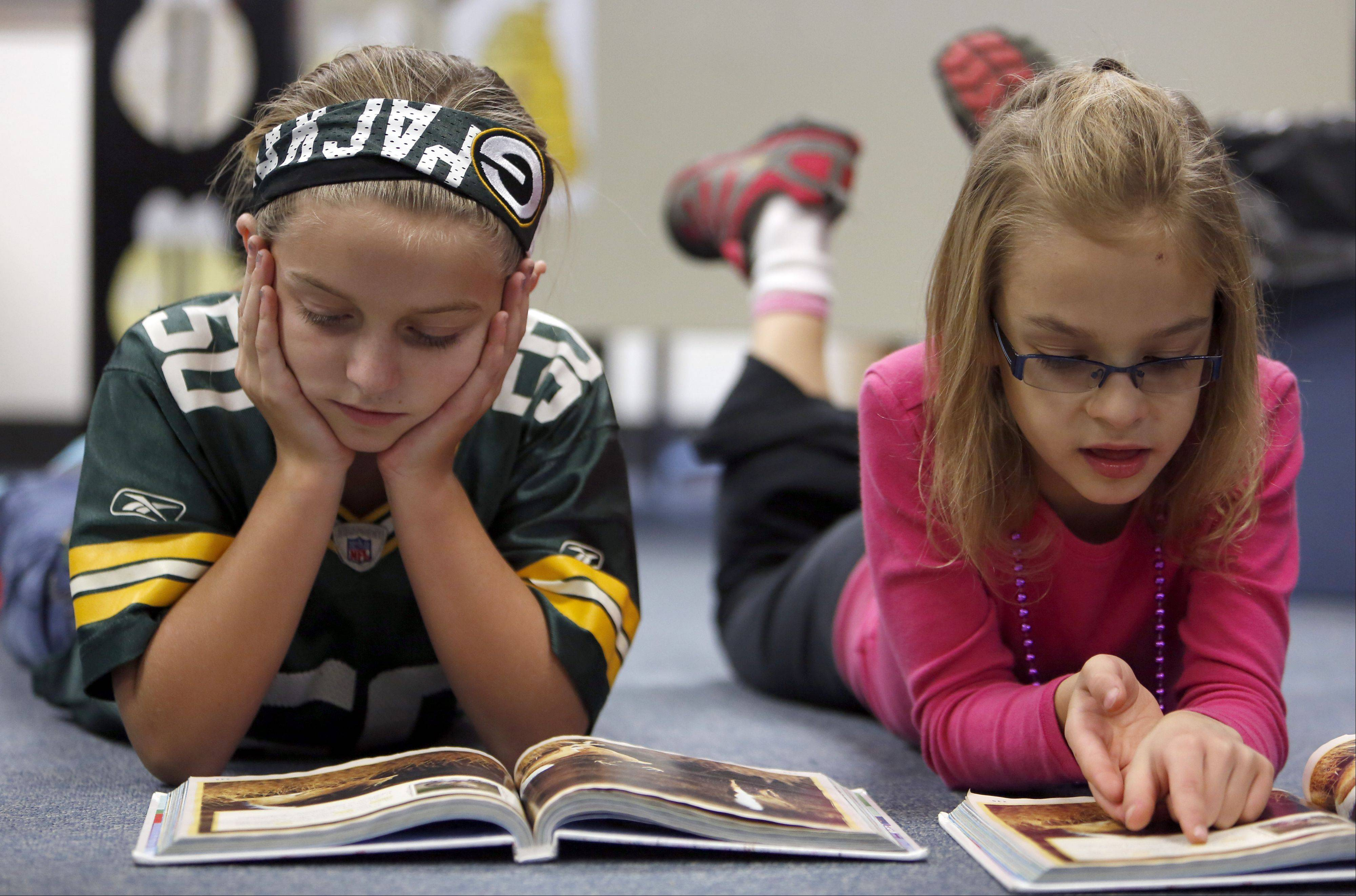 "Brooke Reineking, left, and Stella Petersdorff work on reading at Algonquin Road Elementary School in Fox River Grove. The school's third-graders are at the top of Fox Valley area students ""meeting"" or ""exceeding"" state standards in reading and mathematics."