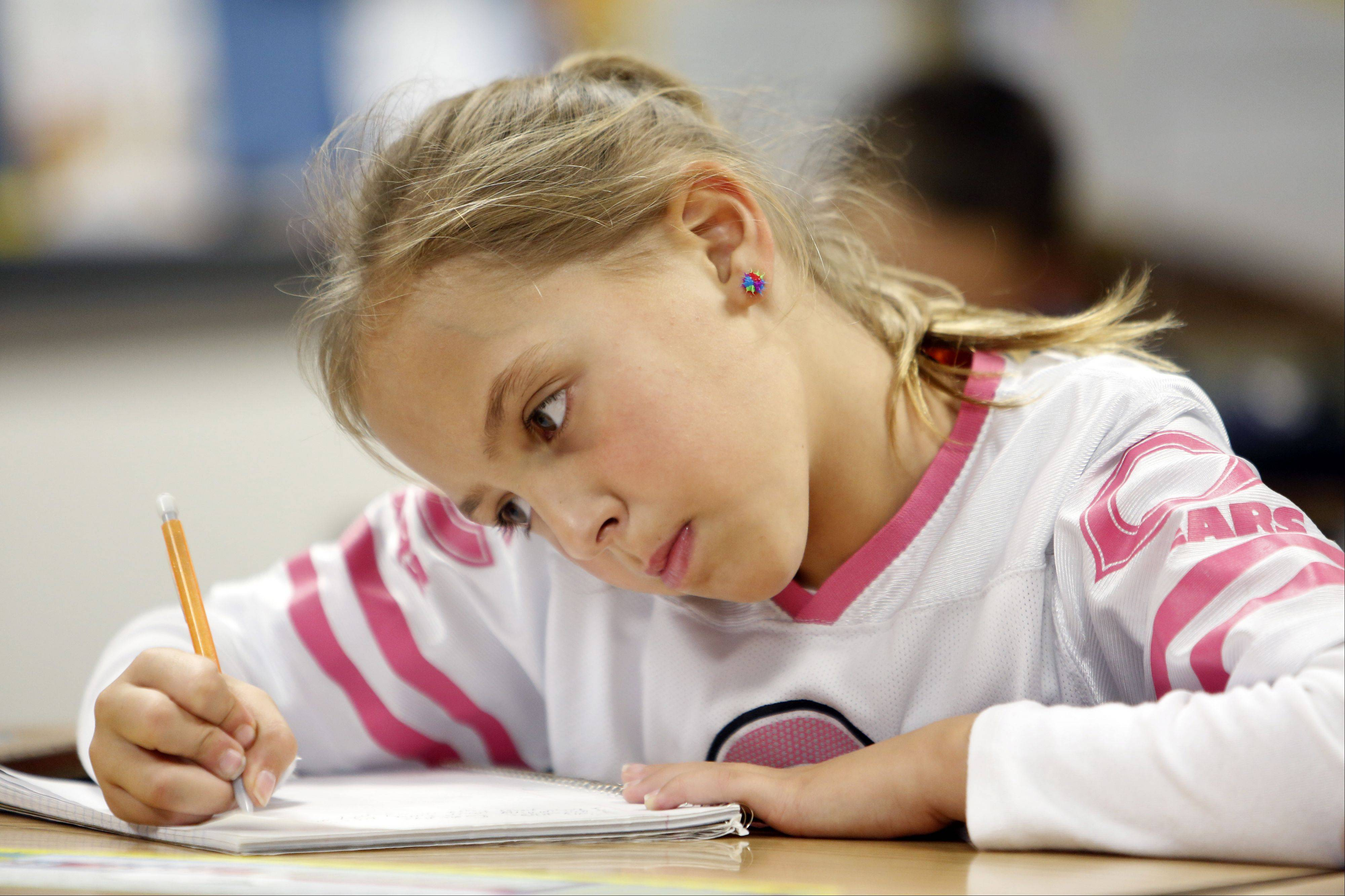 "Third-grader Gabi McCleish writes in her journal Tuesday at Algonquin Road Elementary School in Fox River Grove. The school's third-graders are at the top of Fox Valley area students ""meeting"" or ""exceeding"" state standards in reading and mathematics."