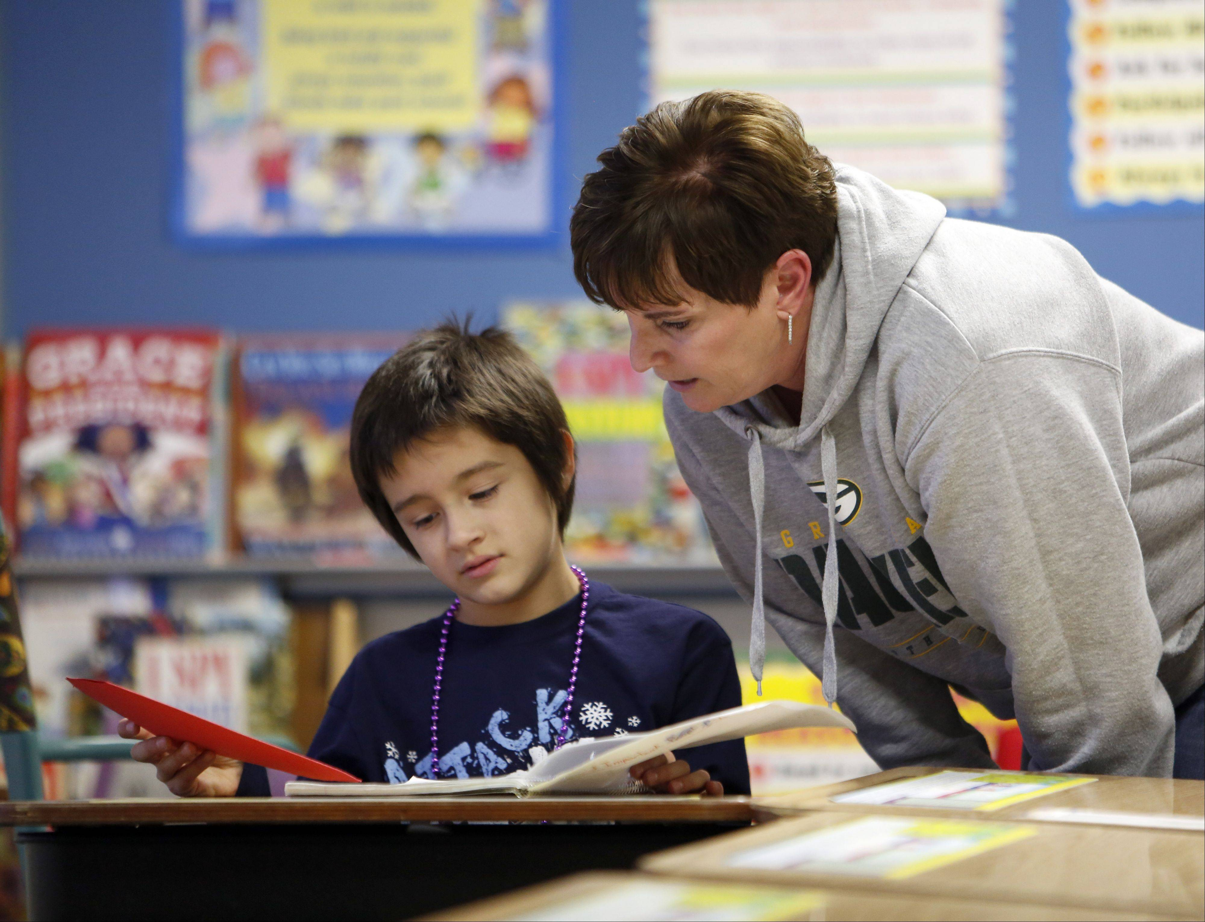 "Third-grade teacher Barb Savage works with Marco Conti at Algonquin Road Elementary School in Fox River Grove. The school's third graders are at the top of students in the Fox Valley area ""meeting"" or ""exceeding"" state standards in reading and mathematics."