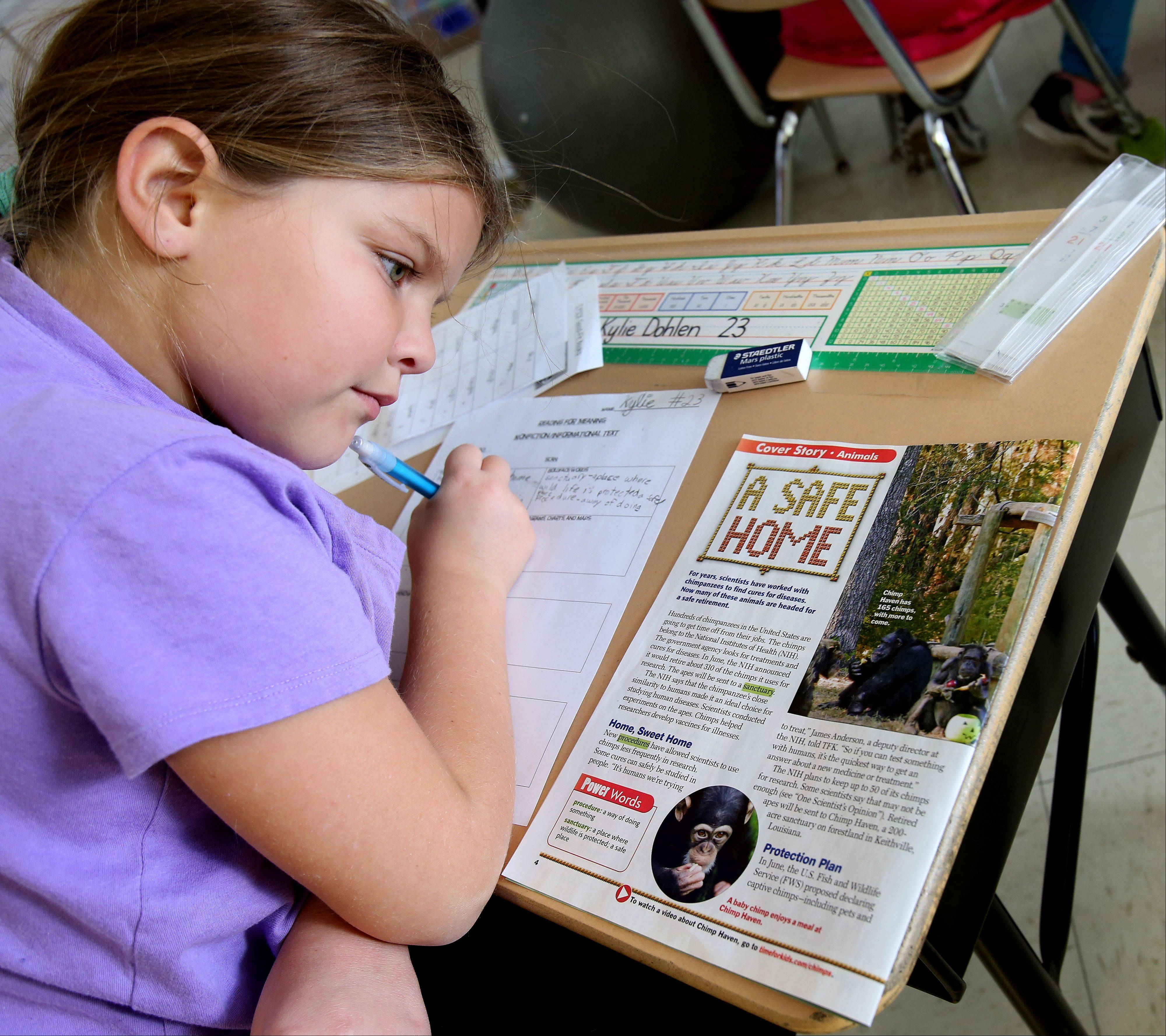 "Kylie Dohlen, a third-grader at Longfellow Elementary in Wheaton, takes notes from a ""Time for Kids"" magazine. The school bought new informational texts to match the Common Core curriculum's focus on reading nonfiction and help students better prepare for standardized tests."