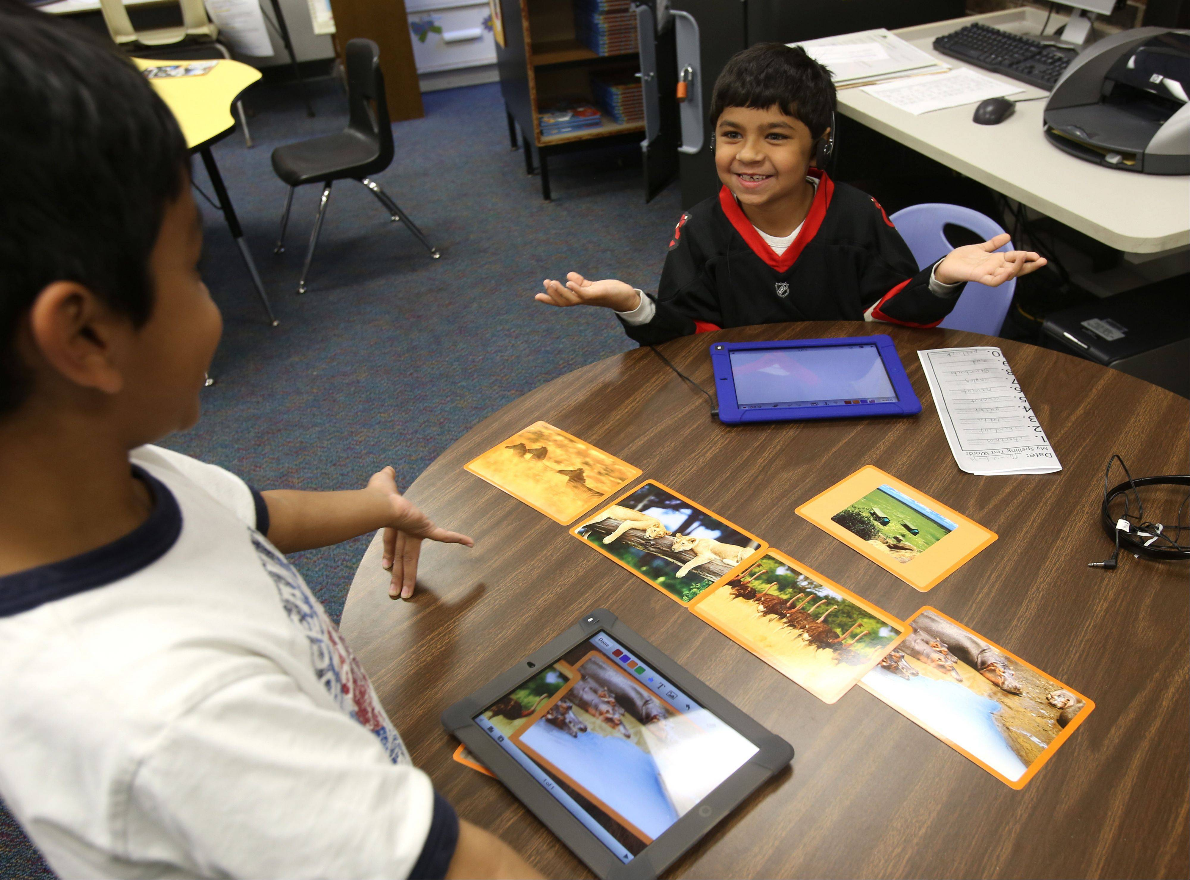 Third-grader students Faris Khan and Rayjan Prakash work on iPads at Brook Forest Elementary in Oak Brook. Principal Kelly Voliva said the school uses technology in some cases to help teachers challenge gifted students, assist struggling students or give assignments for small-group work.