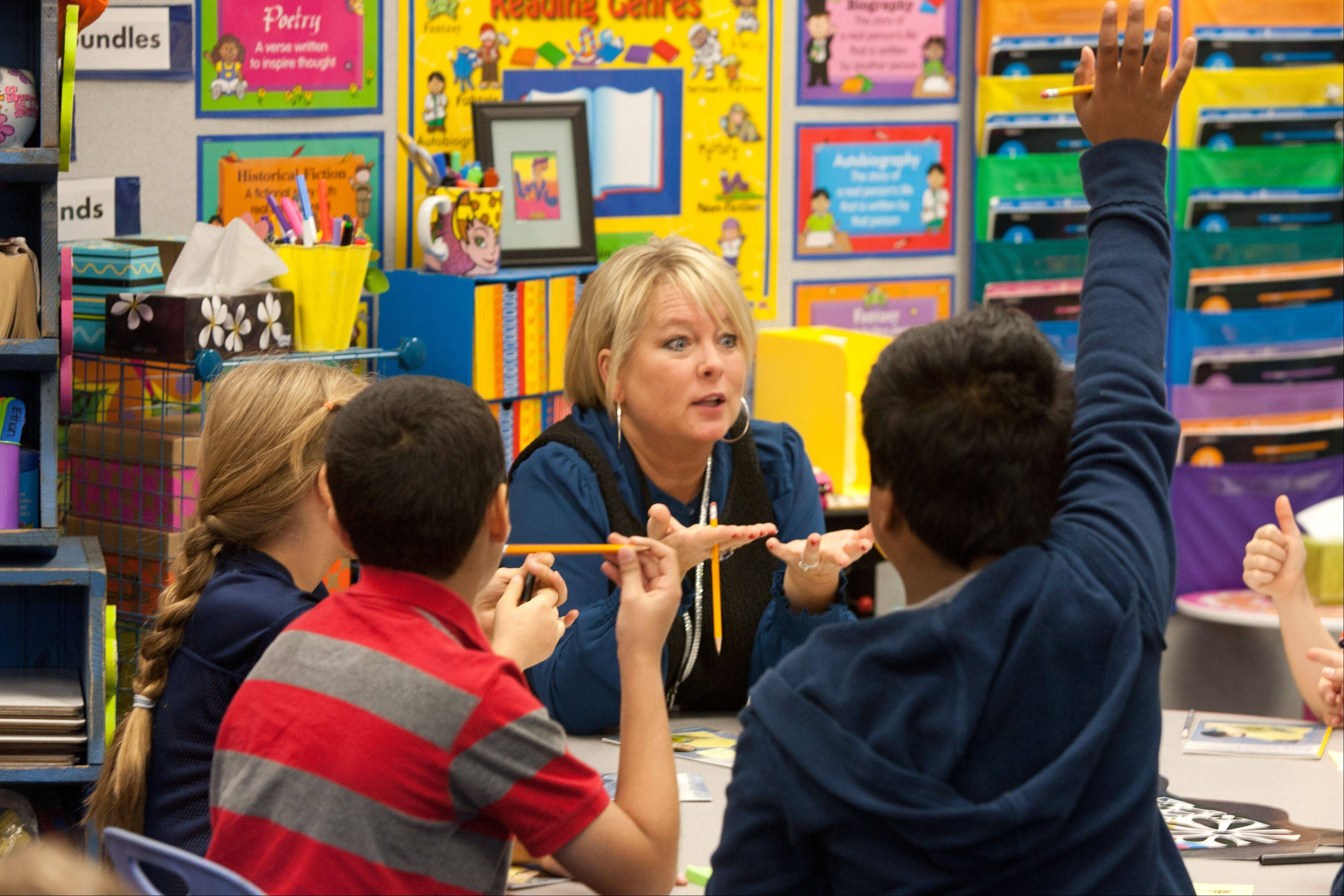 Third-grade teacher Elizabeth Sompolski works with a small group of students at Brook Forest Elementary in Oak Brook. Brook Forest saw one of the smallest decreases in DuPage County in students who meet or exceed testing standards, despite the state's move to increase the cutoff scores necessary to qualify as meeting or exceeding.