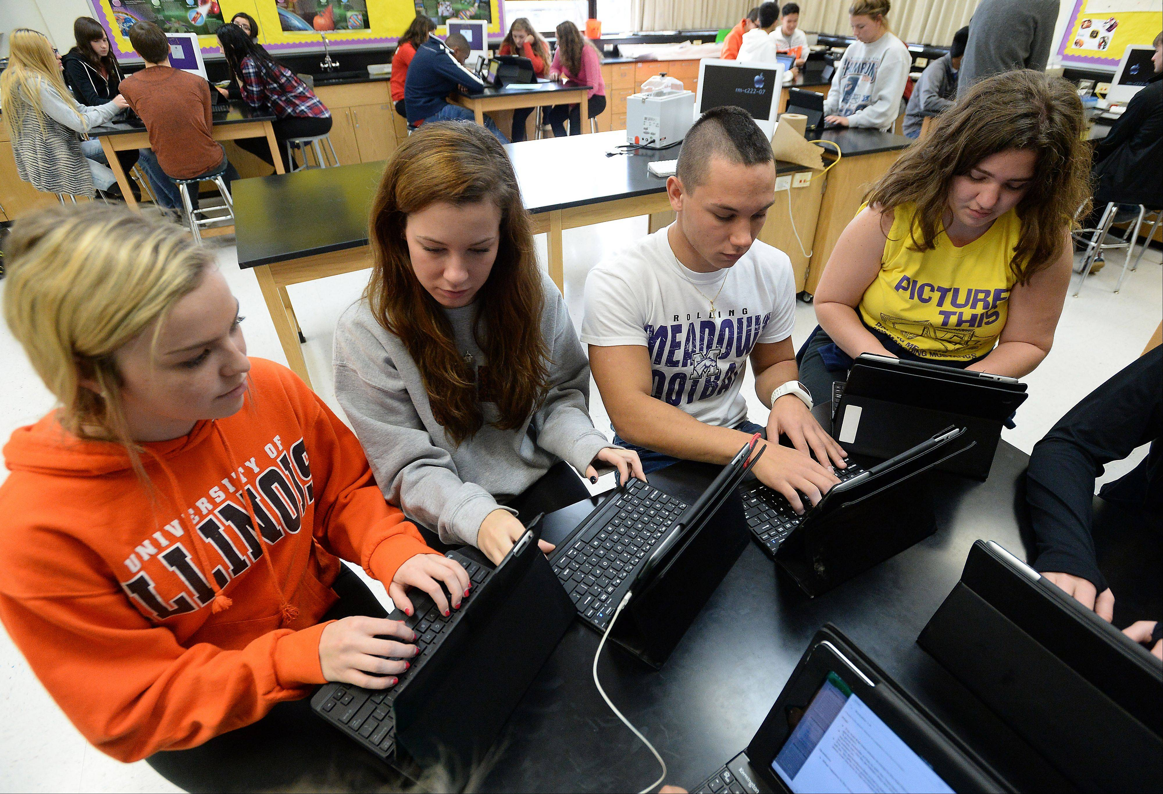 Advanced Placement biology students, from left, Shannon Gavin, Chloe Swindells, Will Hoppe and Desdemona Alvarez use iPads to study evolution at Rolling Meadows High School. Rolling Meadows is among high schools showing increases in the number of students who meet or exceed state testing standards.