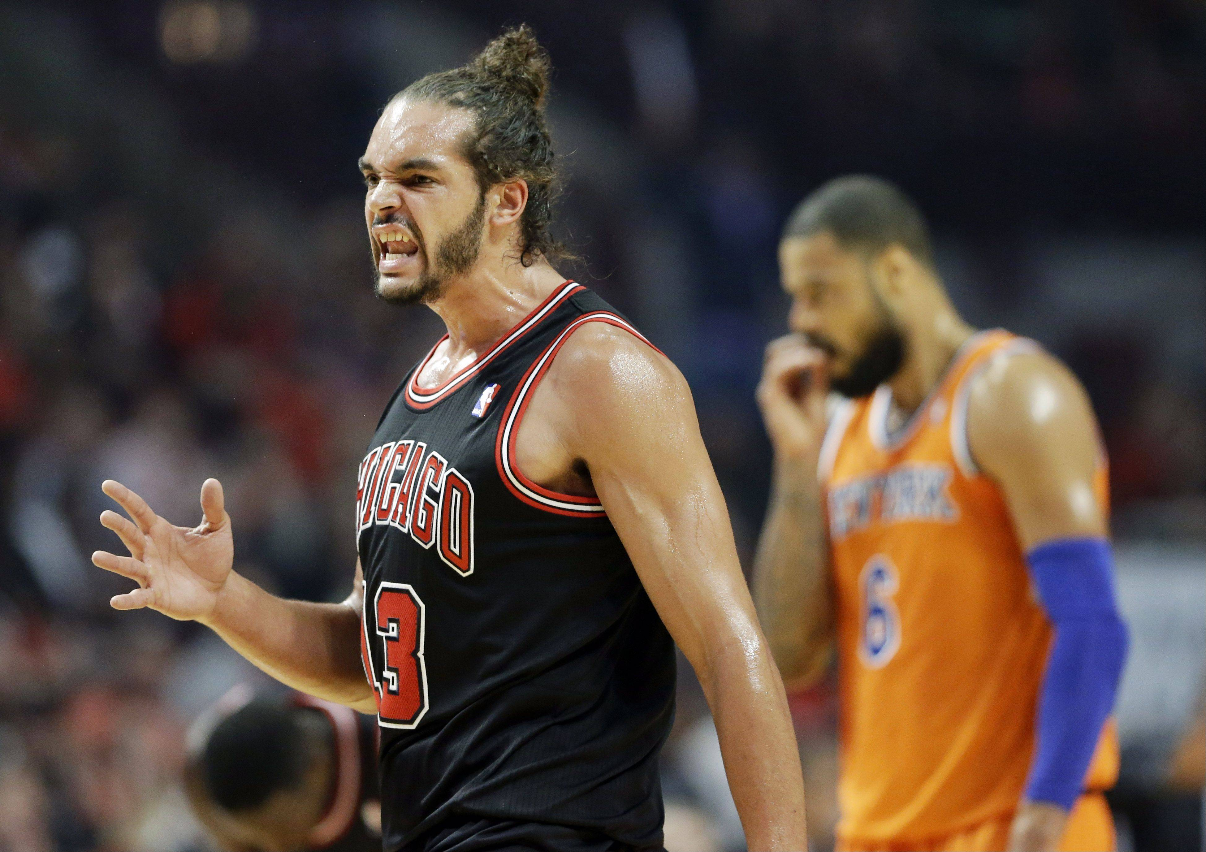 Chicago Bulls center Joakim Noah, left, reacts after Derrick Rose scored a basket as New York Knicks center Tyson Chandler is at right during the first half of an NBA basketball game in Chicago, Thursday, Oct. 31, 2013.