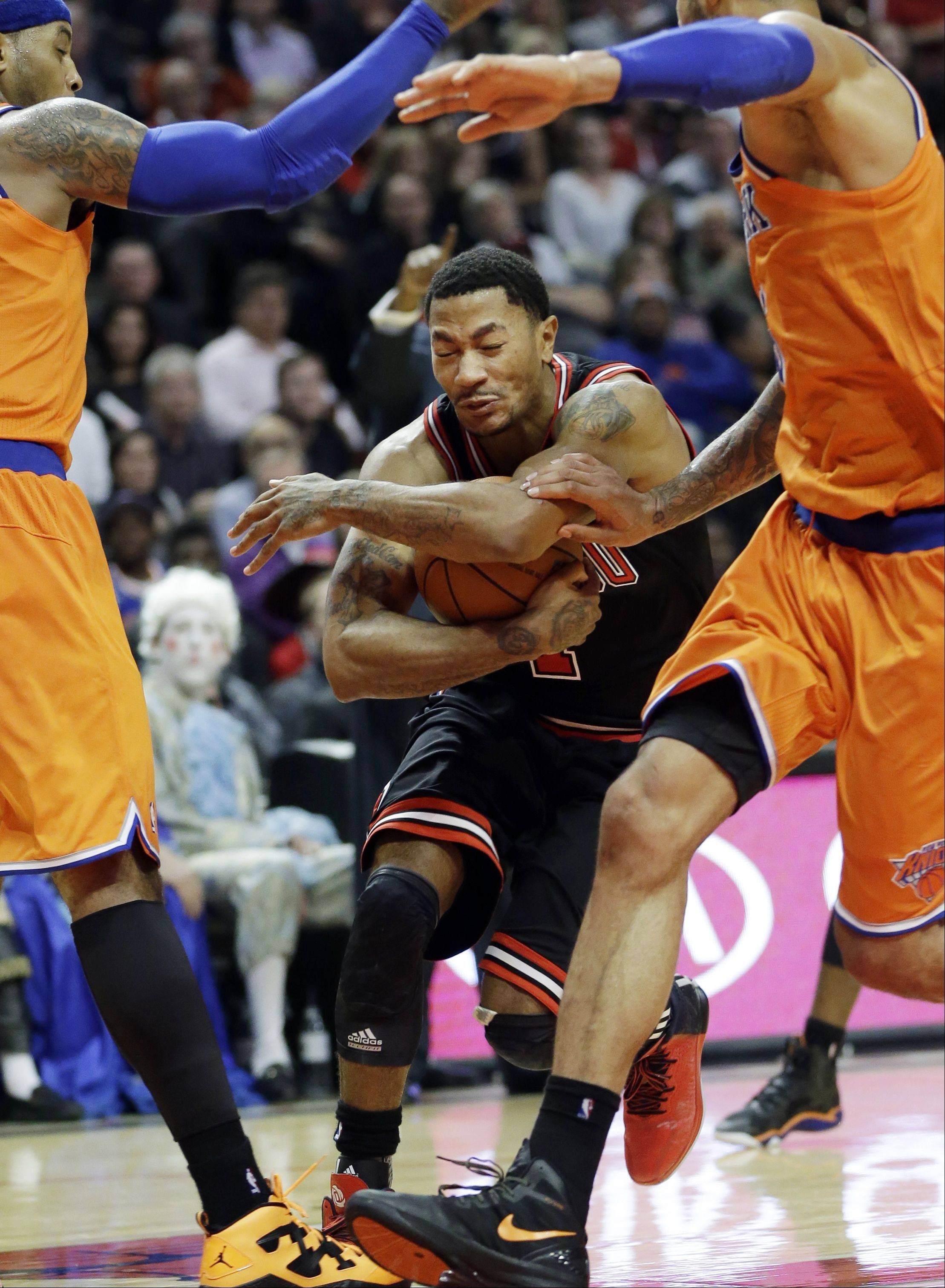 Chicago Bulls guard Derrick Rose, center, drives to the basket between New York Knicks forward Carmelo Anthony, left, and center Tyson Chandler during the second half.