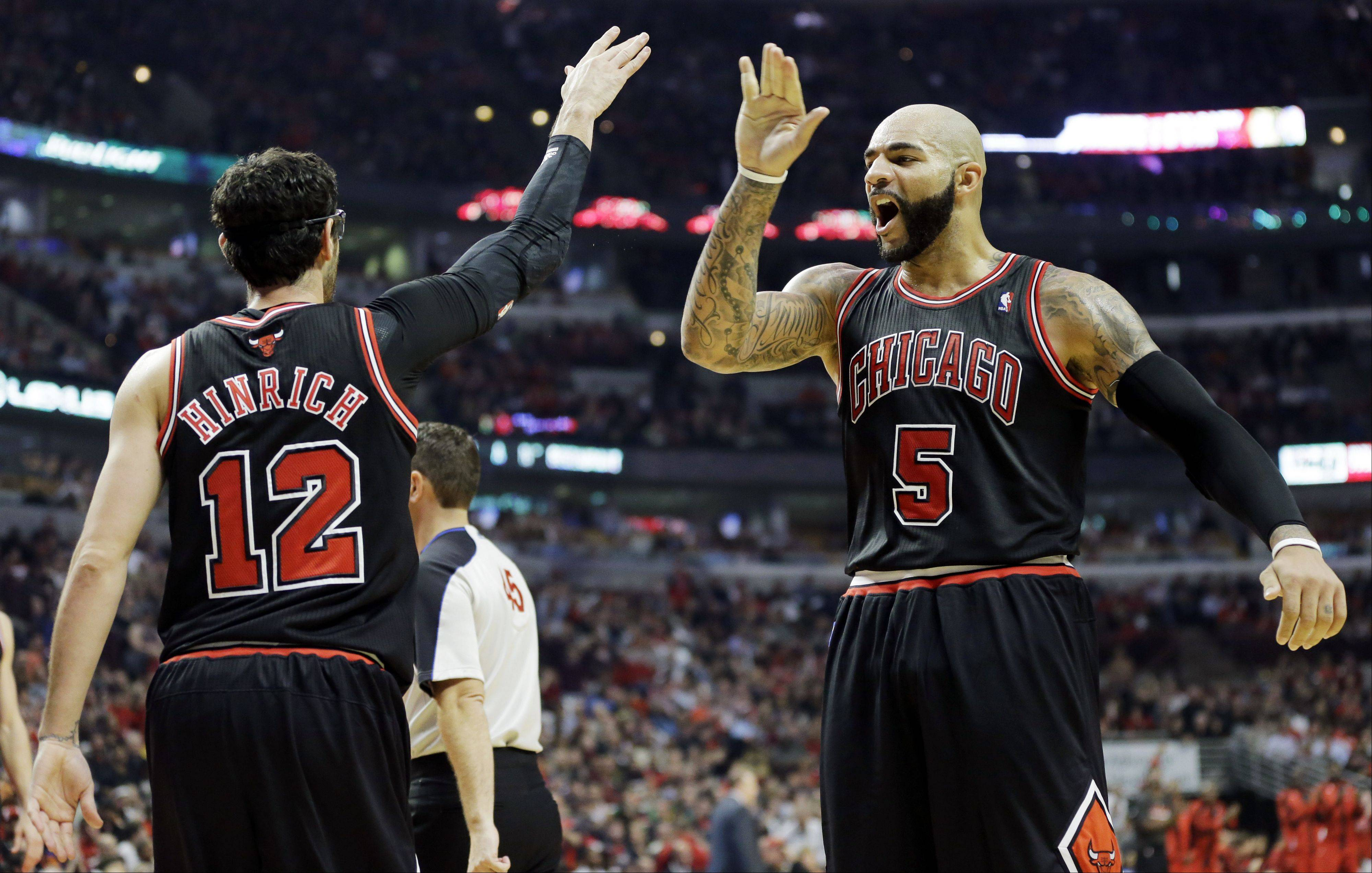 Chicago Bulls guard Kirk Hinrich (12) celebrates with forward Carlos Boozer after scoring a basket during the second half.