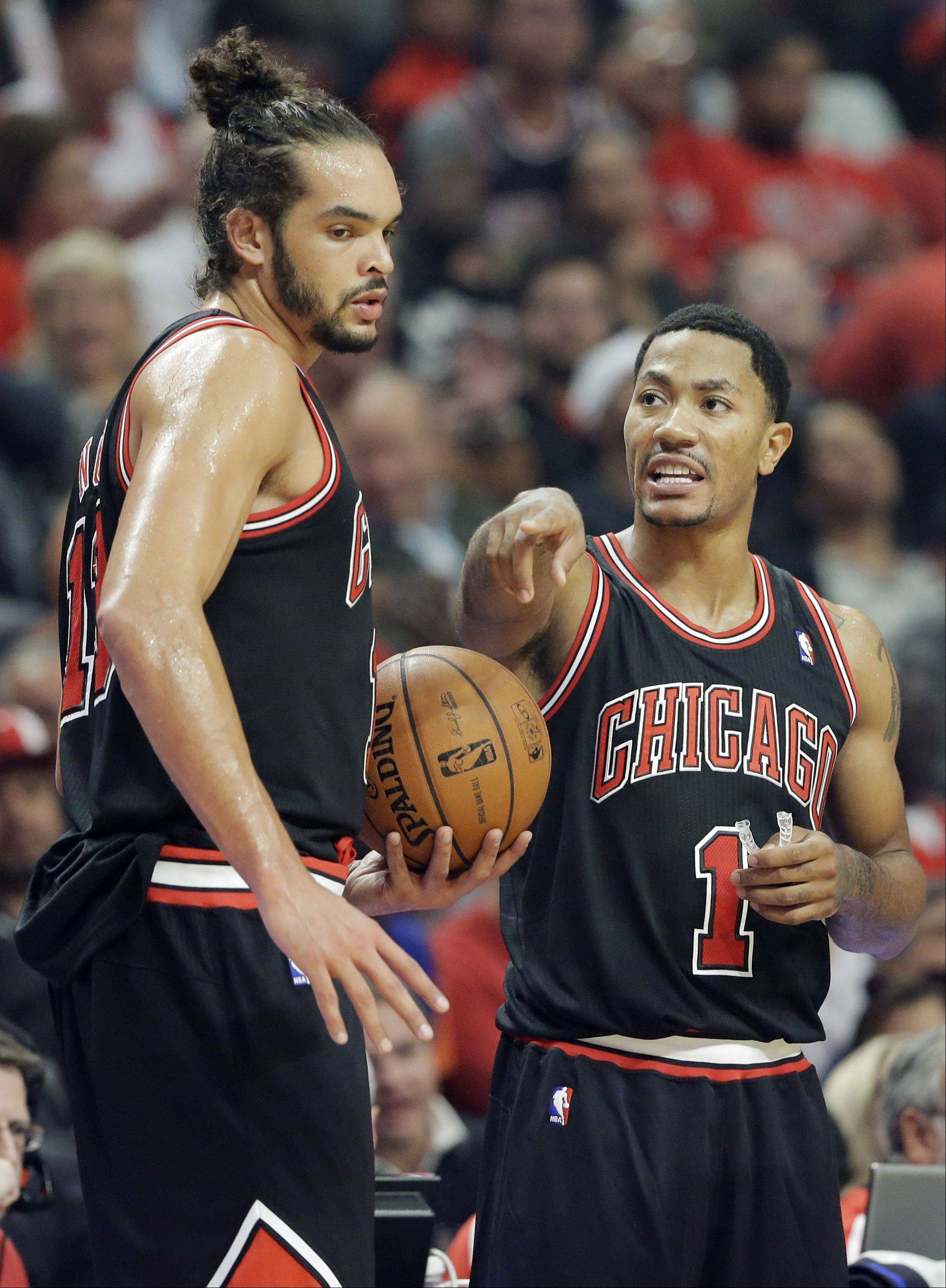 Chicago Bulls guard Derrick Rose, right, talks with center Joakim Noah during the first half of an NBA basketball game against the New York Knicks.