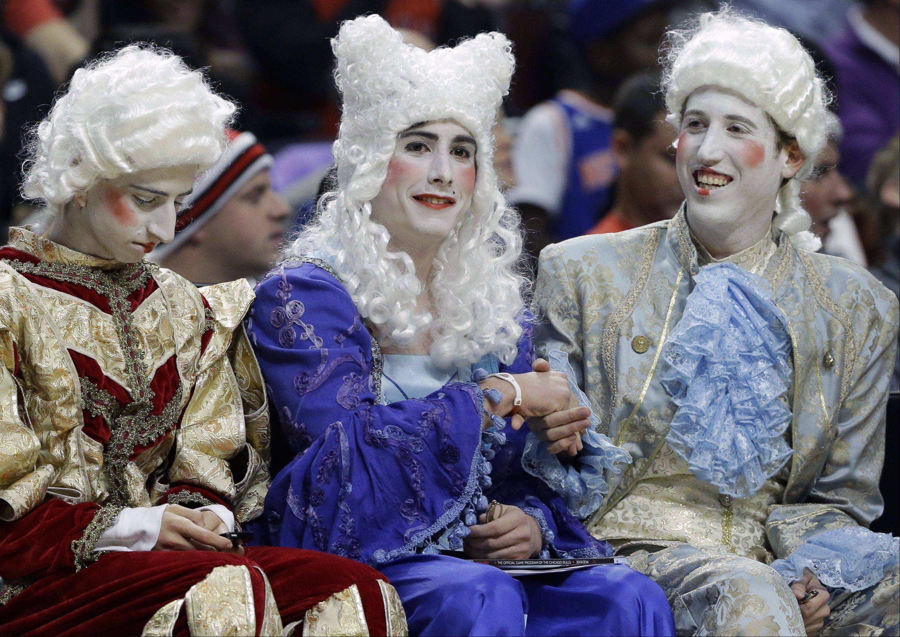 Basketball fans are dressed in Halloween costumes as they watch the New York Knicks and the Chicago Bulls during the first half.