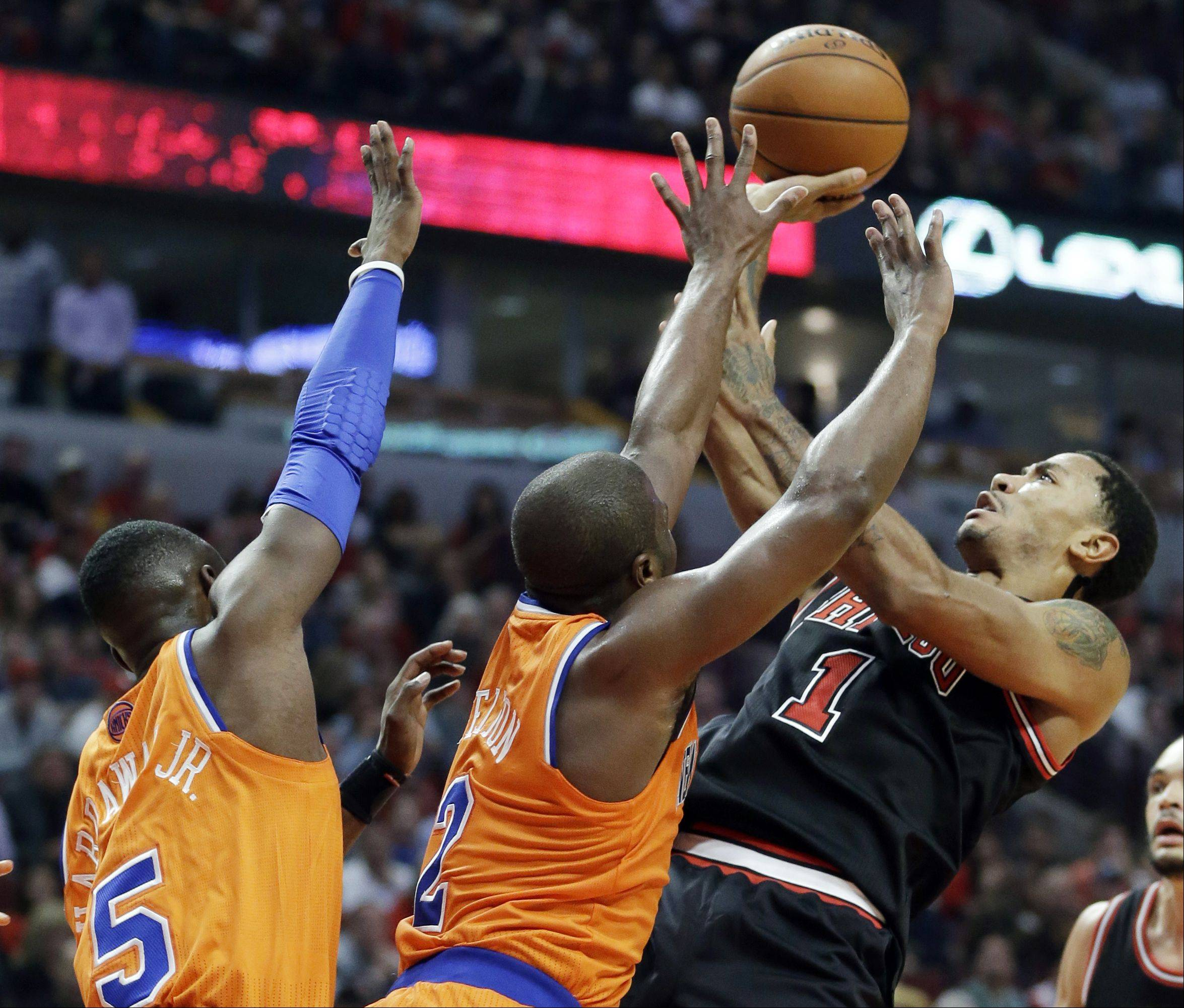 Chicago Bulls guard Derrick Rose (1) shoots over New York Knicks guard Raymond Felton (2) and guard Tim Hardaway Jr during the second half of an NBA basketball game in Chicago,