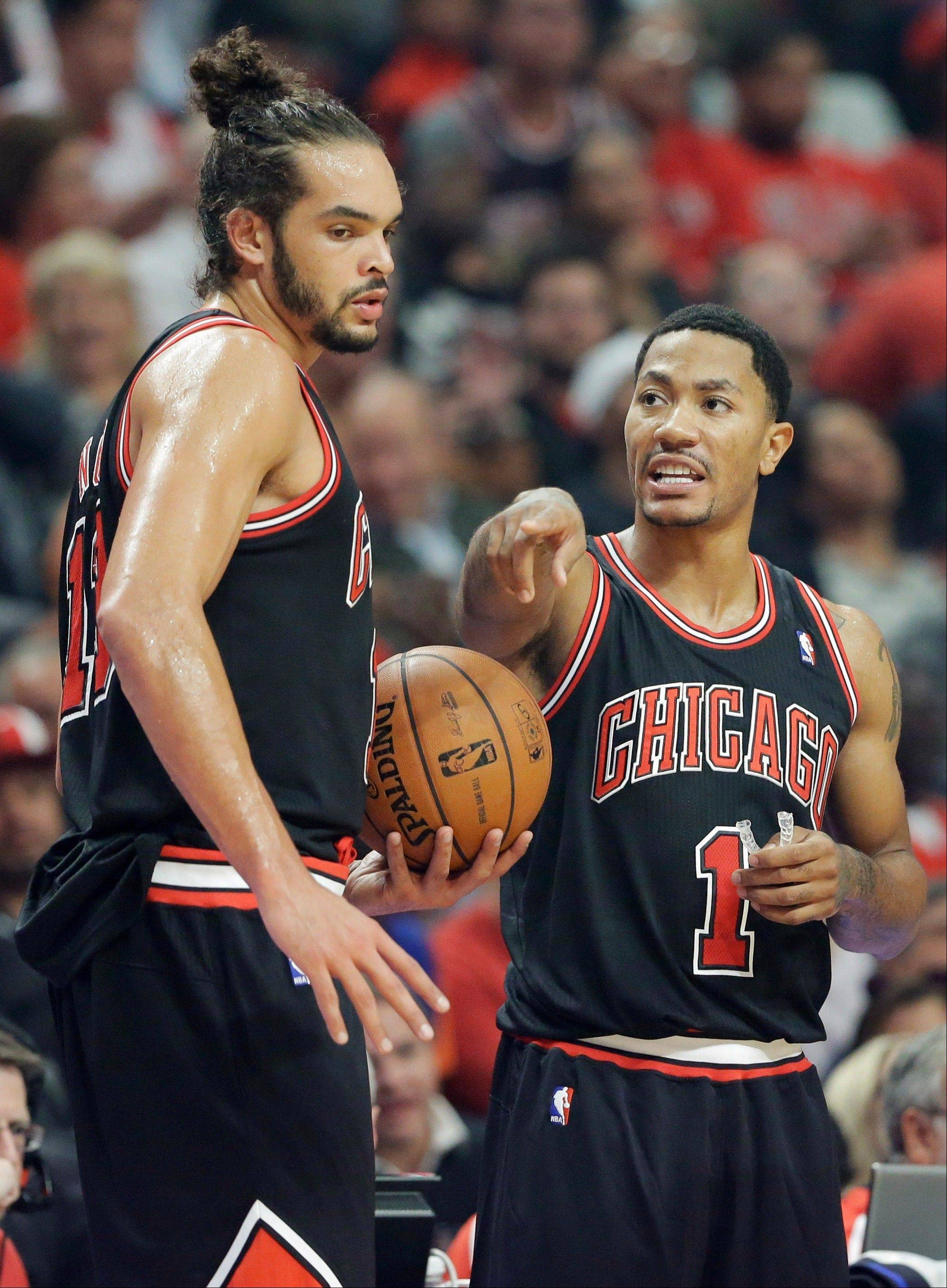 Joakim Noah and Derrick Rose talk a play over in the Bulls's Thursday night win over the New York Knicks at United Center.