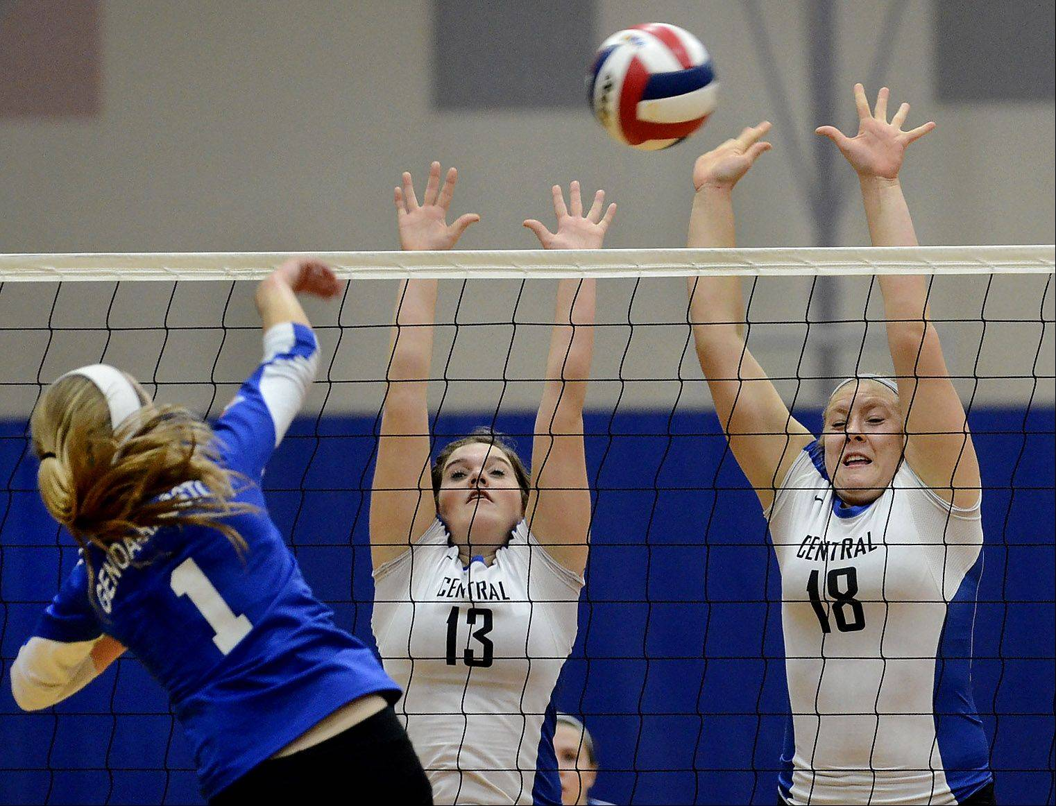 Central's Maddy Barry, left, and Makenna Jensen go for a block of a shot by Bridget Halat, as Burlington Central defeats Genoa-Kingston volleyball for Class 3A regional title.