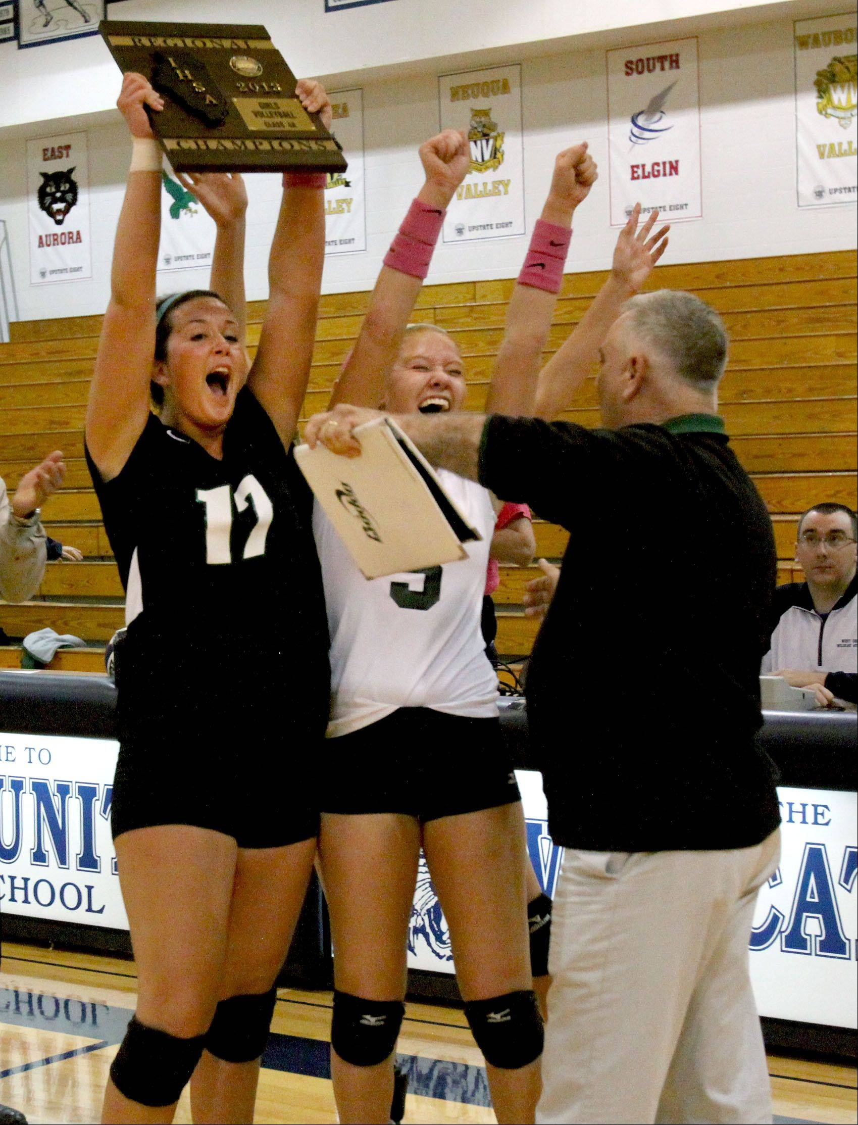Caroline Jenkins, left, Meg DeMaar, right, and coach Peter Mastandrea of Glenbard West celebrate their win over Schaumburg in the Class 4A regional volleyball final in West Chicago on Thursday.