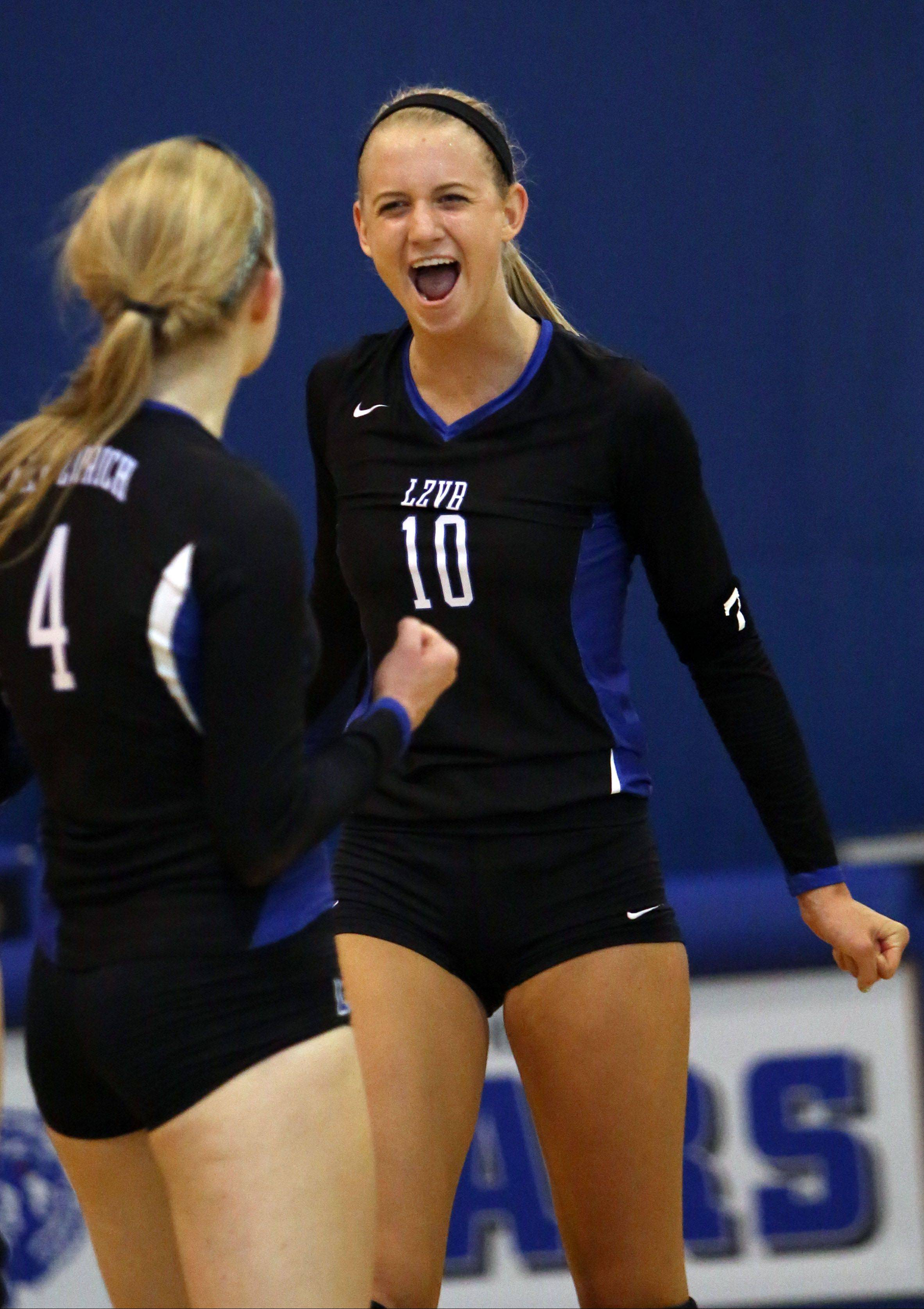 Lake Zurich's Kristen Walding, right, celebrates with teammate Kiley McPeek after winning a point in a matchup against Carmel.
