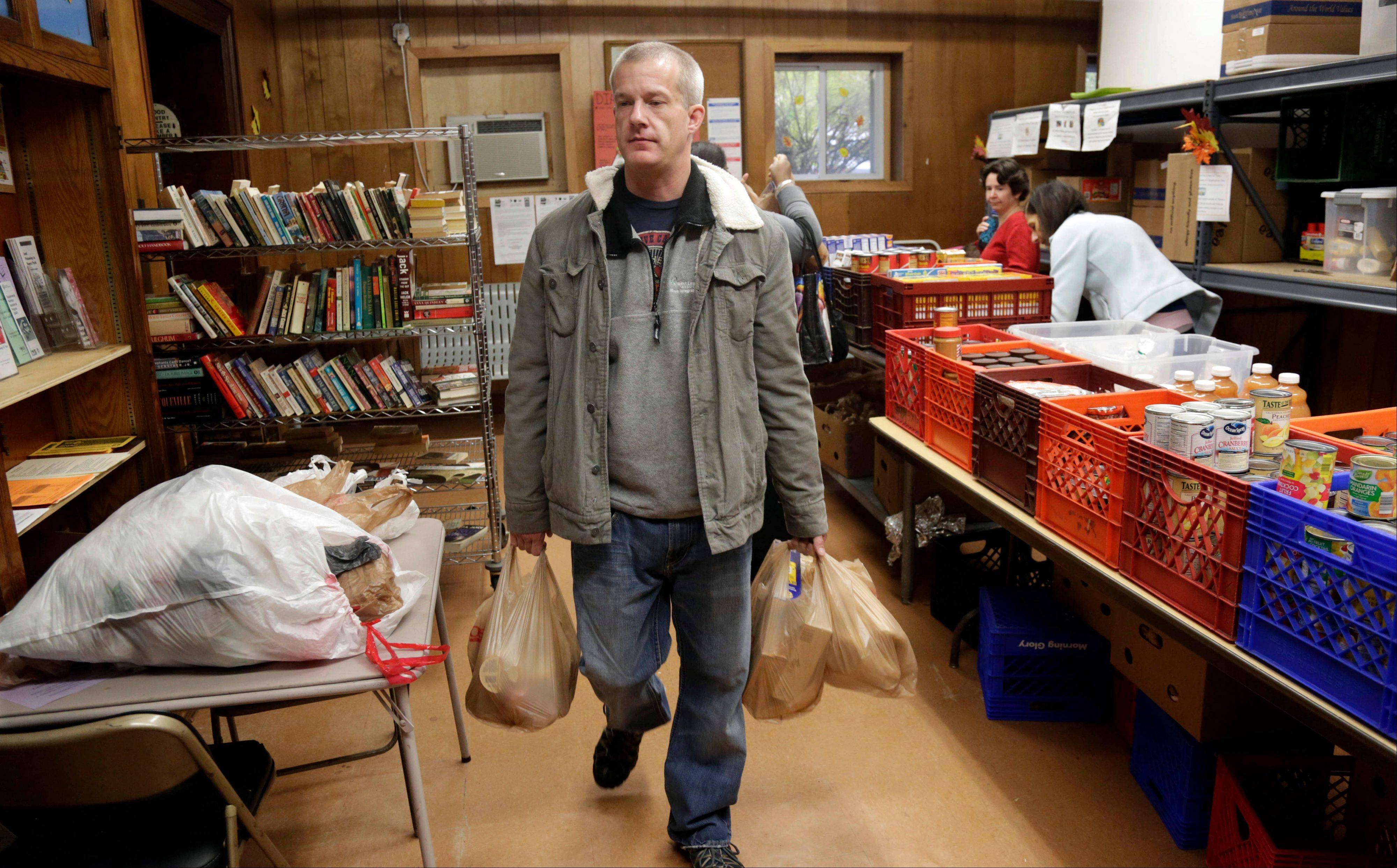 Larry Bossom, 41, who lost his job a few month ago, leaves the St. Ignatius food pantry Friday with bags of items. Bossom is relying on food stamps and the food bank to help him until he finds work again.
