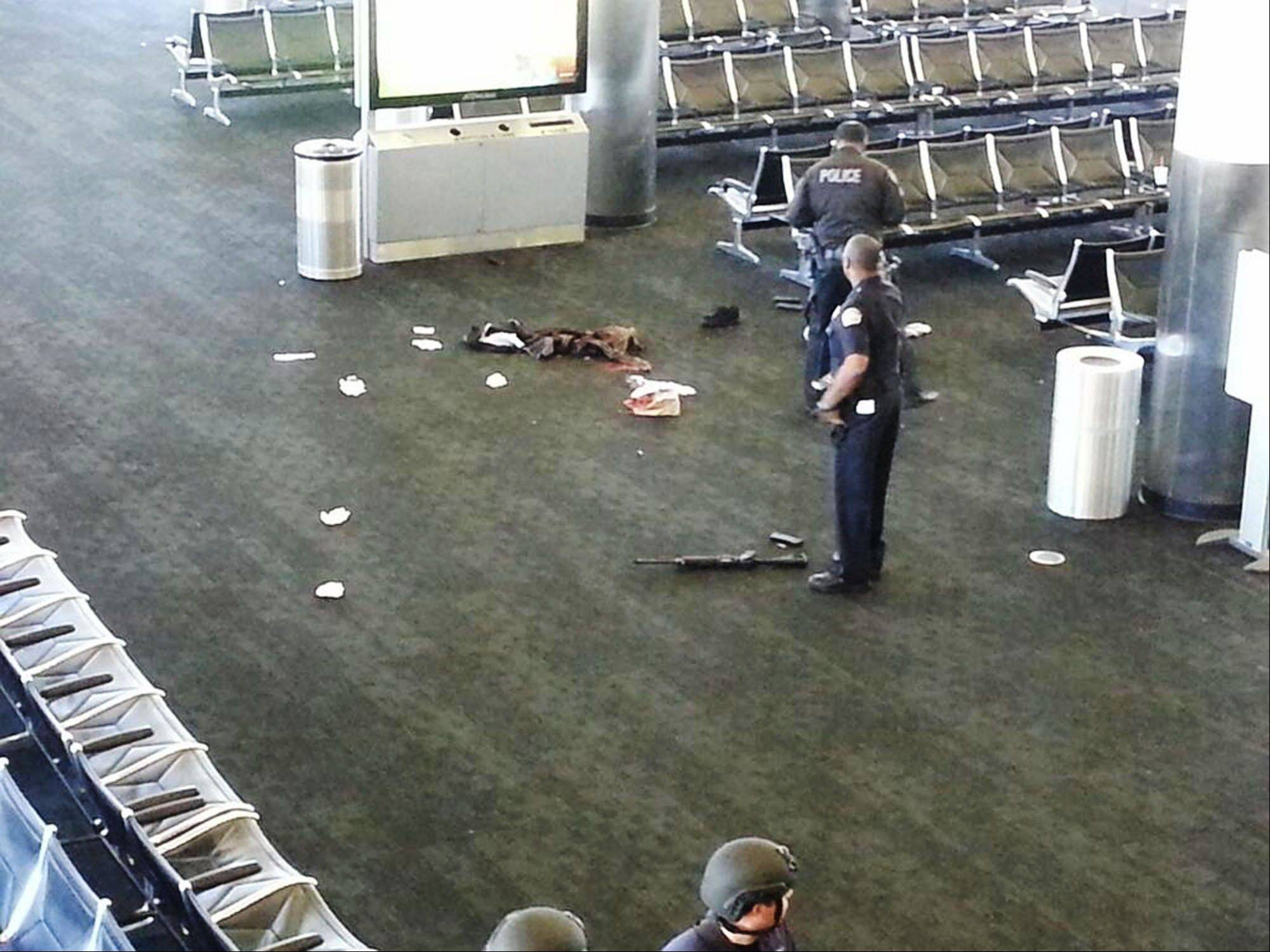 Police officers stand Friday near an unidentified weapon in Terminal 3 of the Los Angeles International Airport.