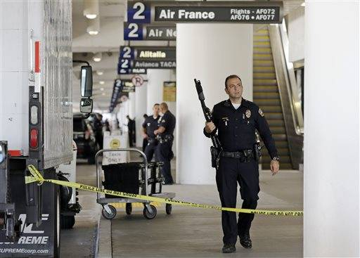Police stand guard in Terminal 2 at Los Angeles International Airport on Friday, Nov. 1, 2013. A gunman armed with a semi-automatic rifle opened fire at the airport on Friday, killing a Transportation Security Administration employee and wounding two other people. Flights were disrupted nationwide.