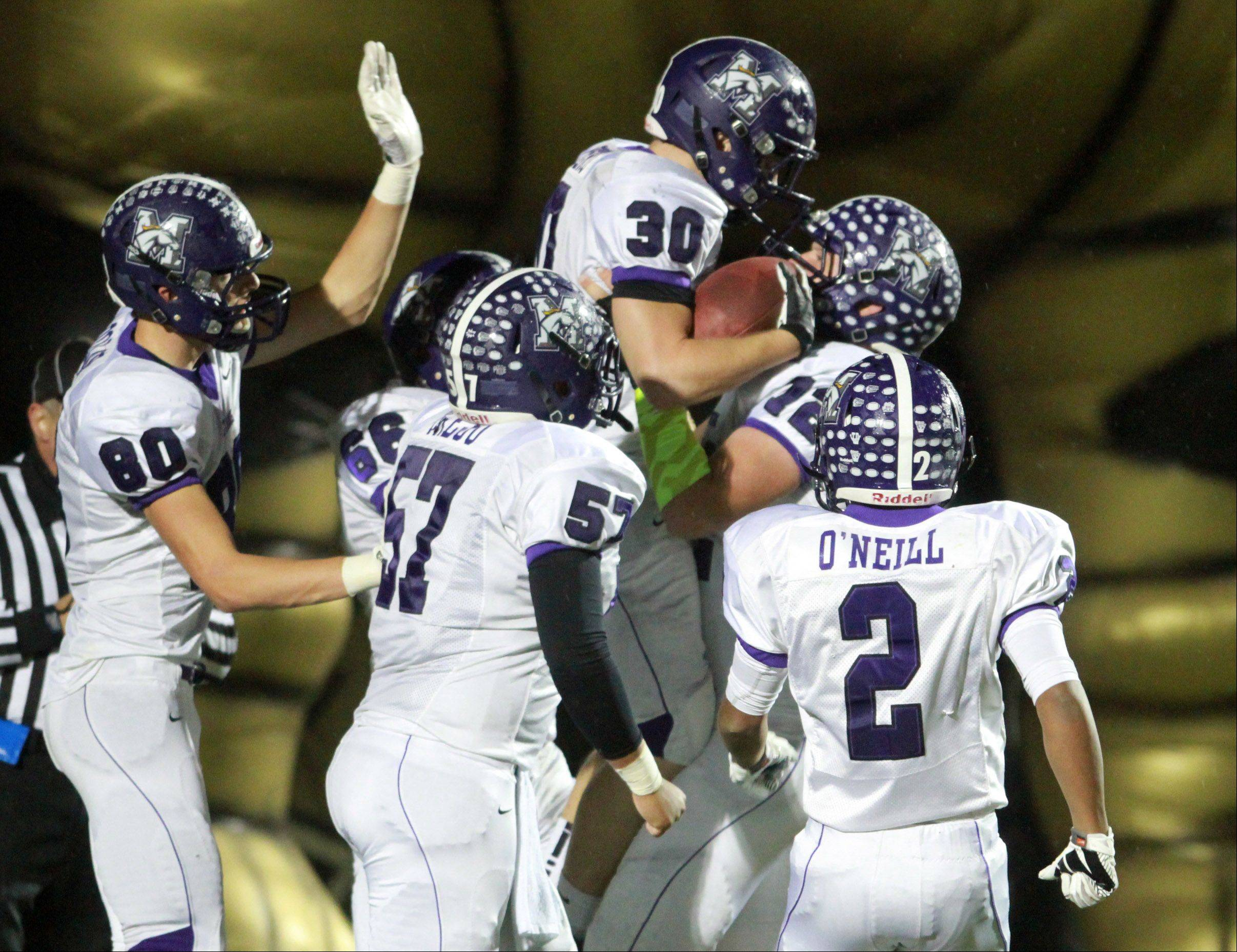 After scoring a touchdown, Rolling Meadows� Kevin Montero leaps into the arms of offensive lineman Greg Off in a Class 6A playoff opener at Grayslake North on Friday.