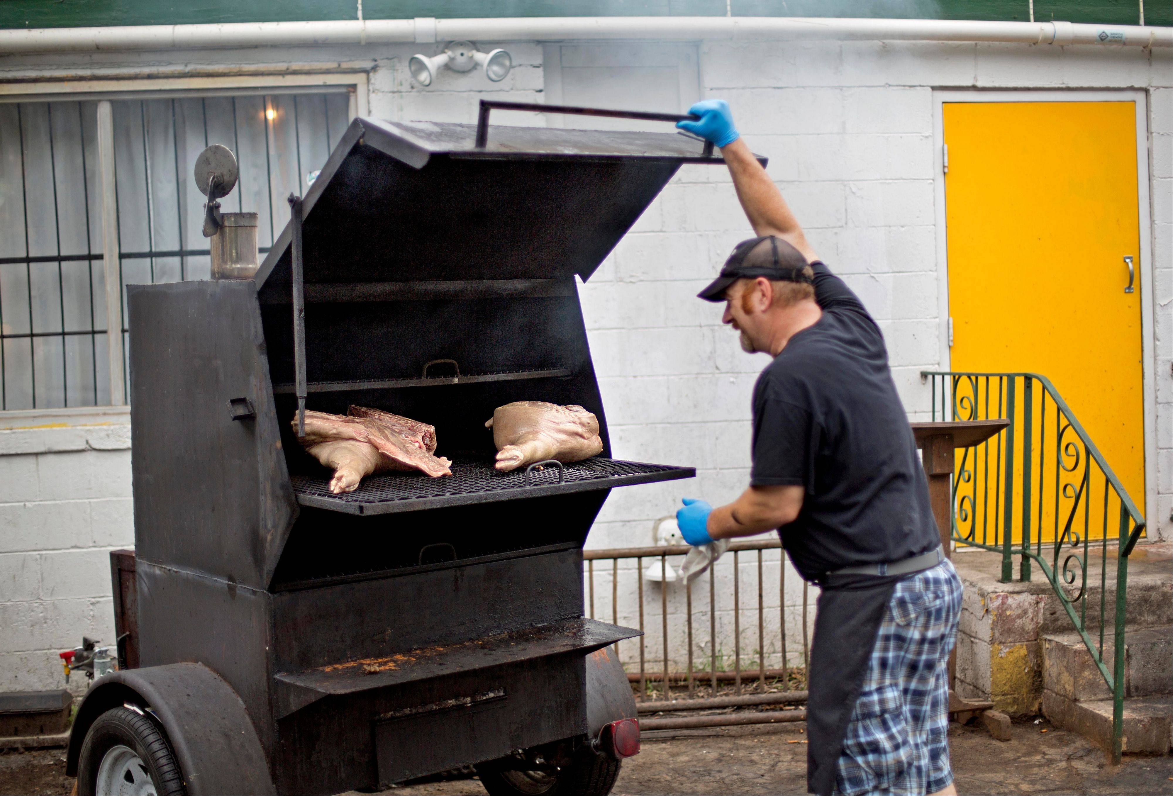 Jim Holycross checks on meat smoking outside Home grown.