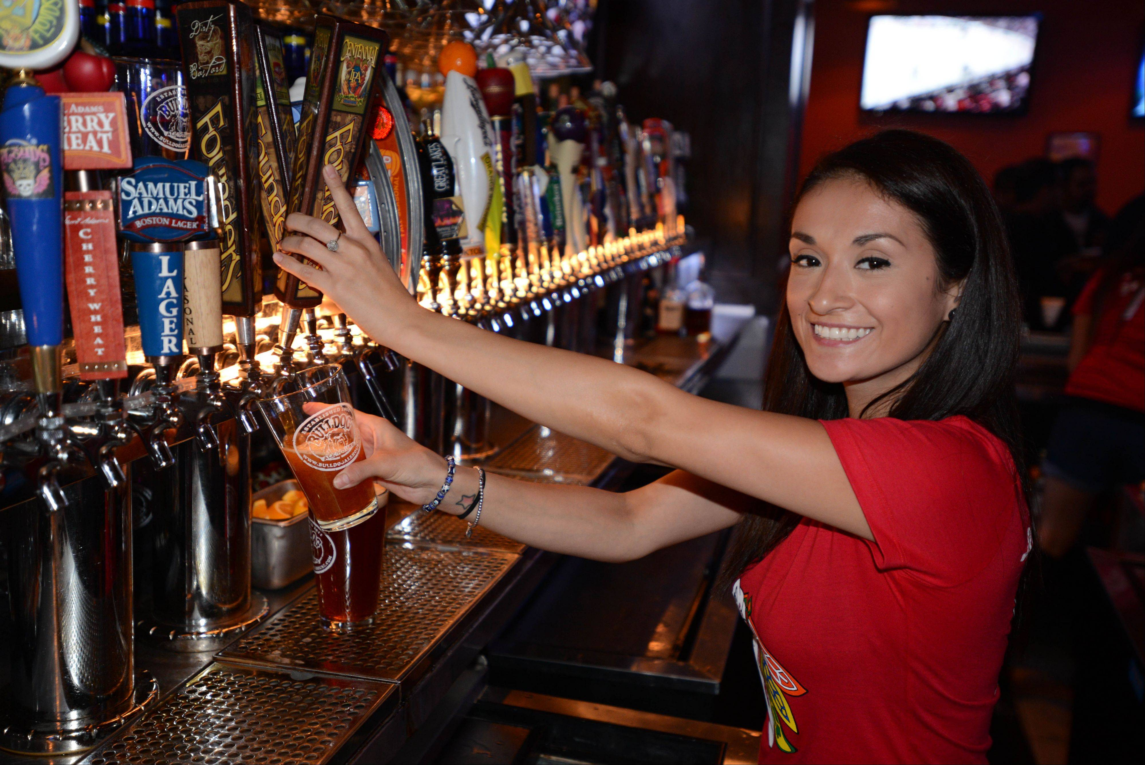 Ana Villegas taps at beer at Bulldog Ale House in Roselle.