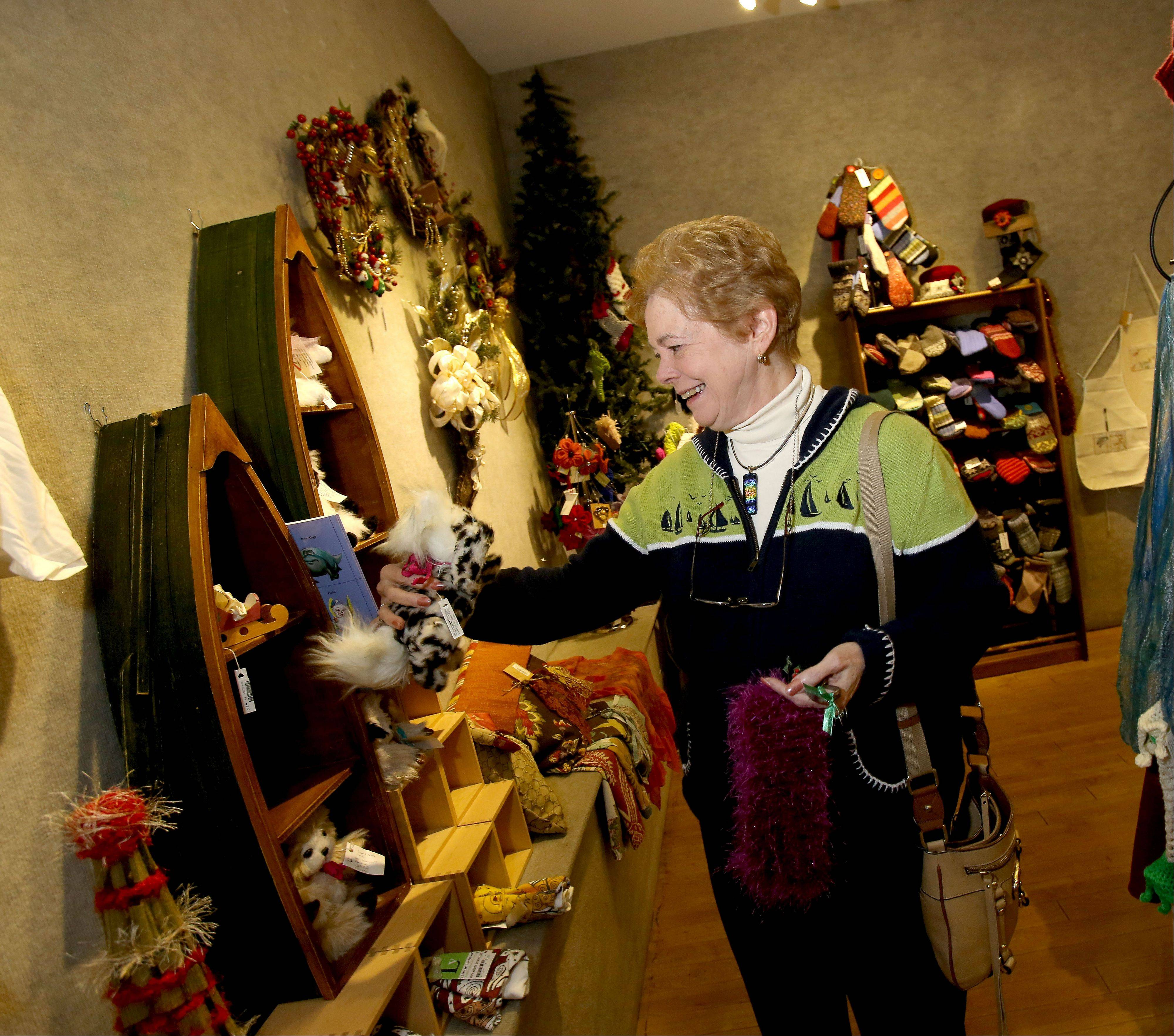 "Penny Linneweh of Glen Ellyn does a little shopping Friday at the ""Yuletide Treasures"" sale at the DuPage Art League in Wheaton. Linneweh is also an art league member and contributor."
