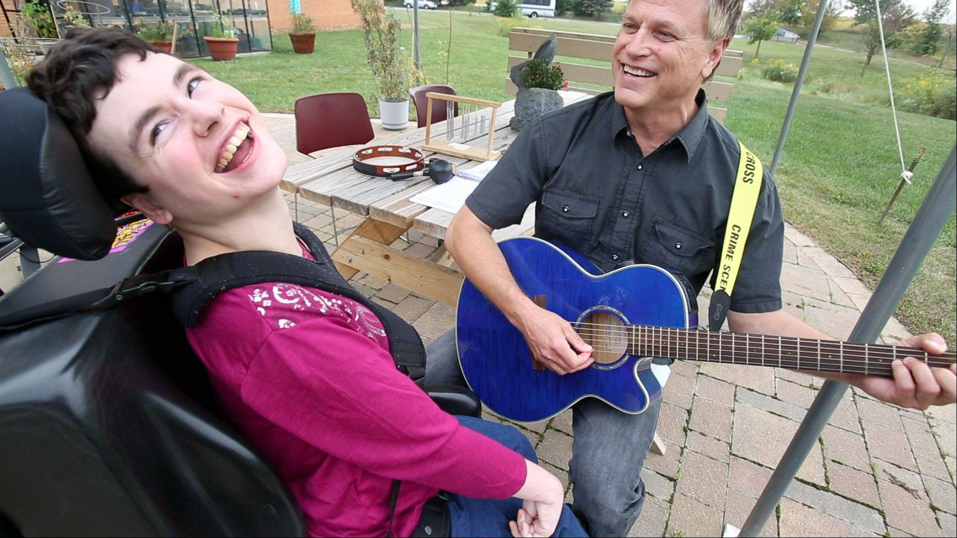 Marklund client Ashley, who has severe developmental disabilities, sings along with Bartlett resident and recreation therapist Wesley Kochan, as he plays his guitar at the center in Geneva.