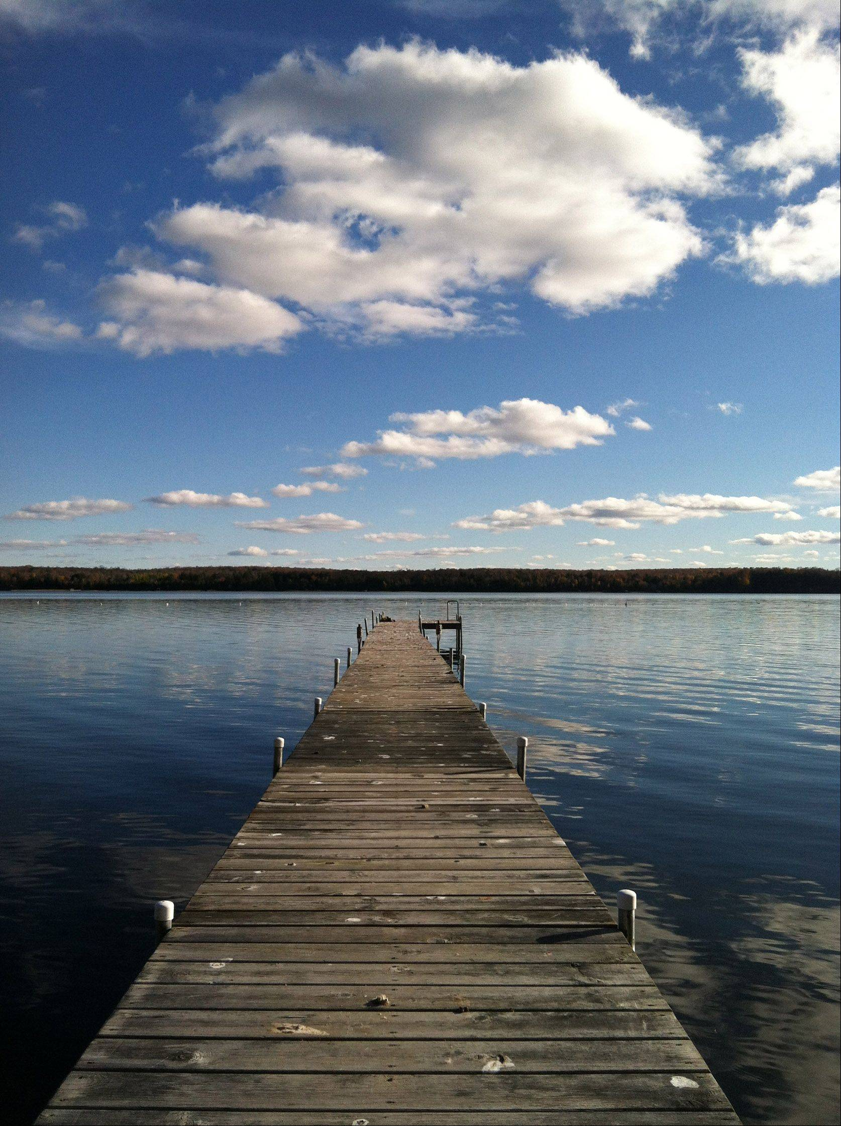A neighbor's pier extends into a still lake with a blue sky and puffy white clouds on October 13th on Big Sand Lake in Phelps, WI