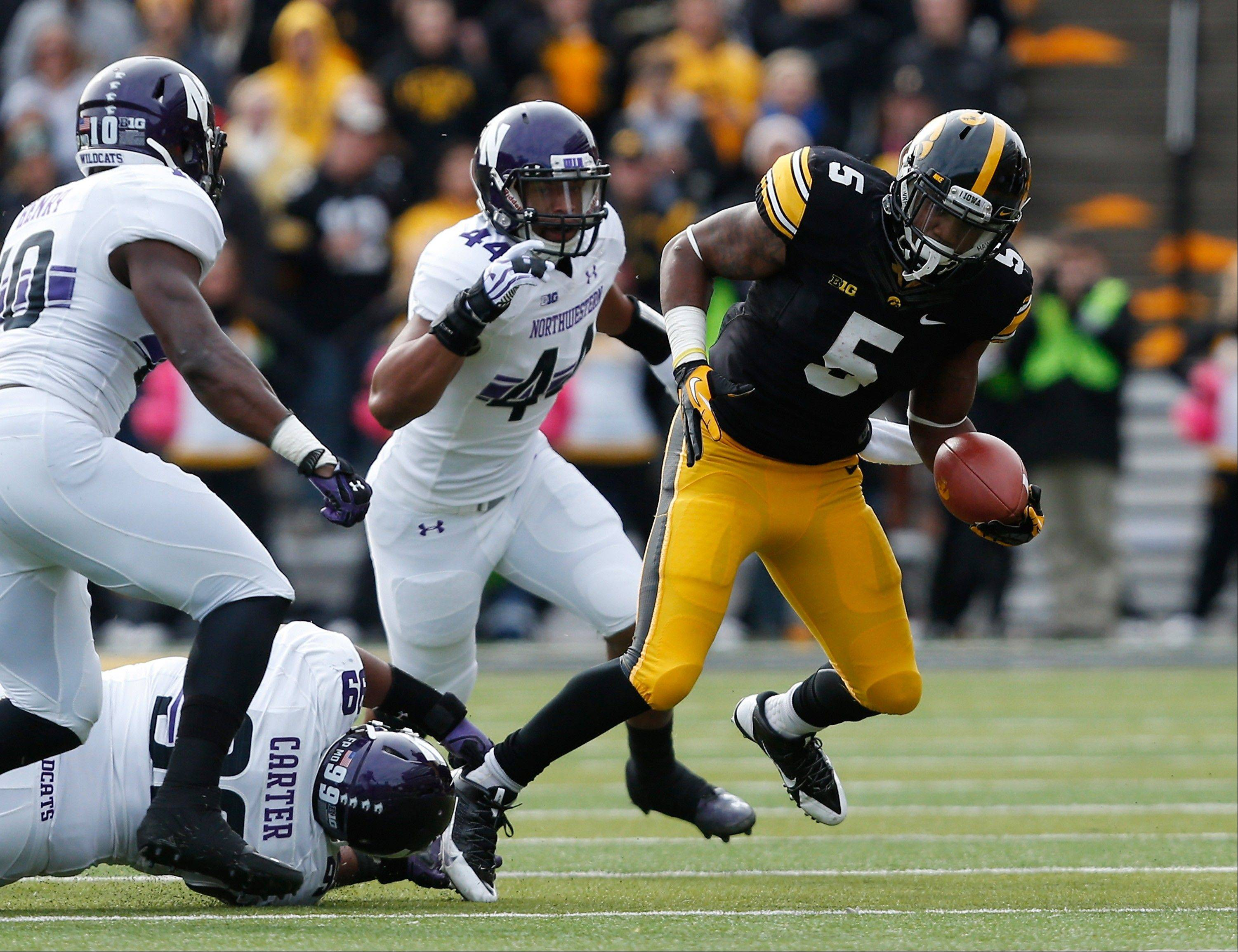 Iowa running back Damon Bullock escapes Northwestern Wildcats defensive lineman Chance Carter during the first half of last Saturday's game in Iowa City.