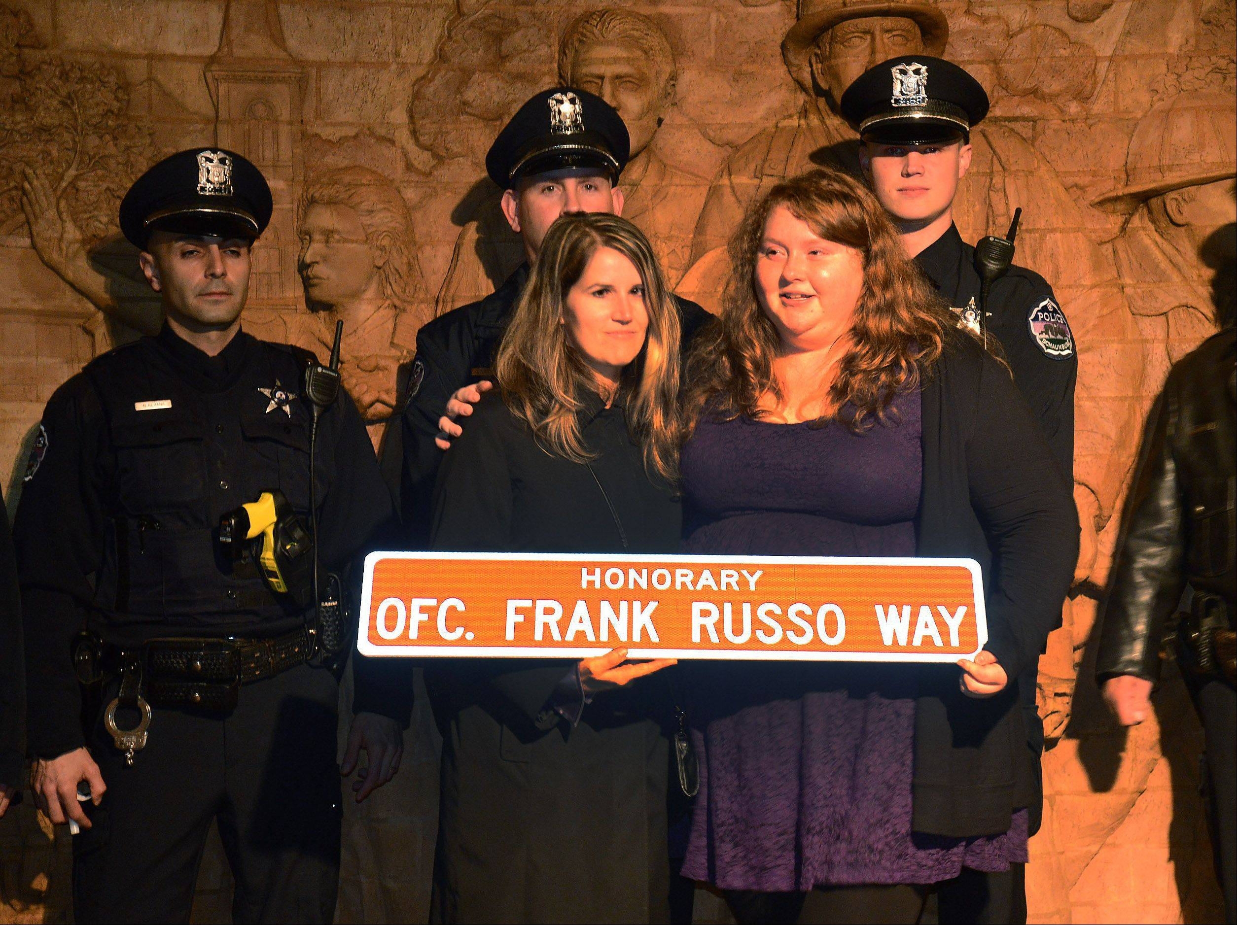Jenny Russo, widow of Frank Russo, left, and Teresa Russo, his daughter, hold the honorary street sign presented to the Russo family during a special ceremony outside the Schaumburg police station on Friday night.