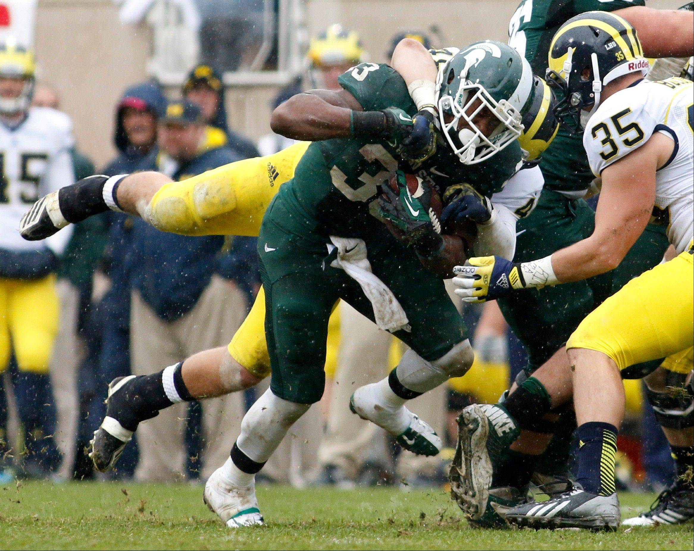 Michigan State's Jeremy Langford (33) is stopped by Michigan's Desmond Morgan, rear, and Joe Bolden (35) during the second quarter in East Lansing, Mich.
