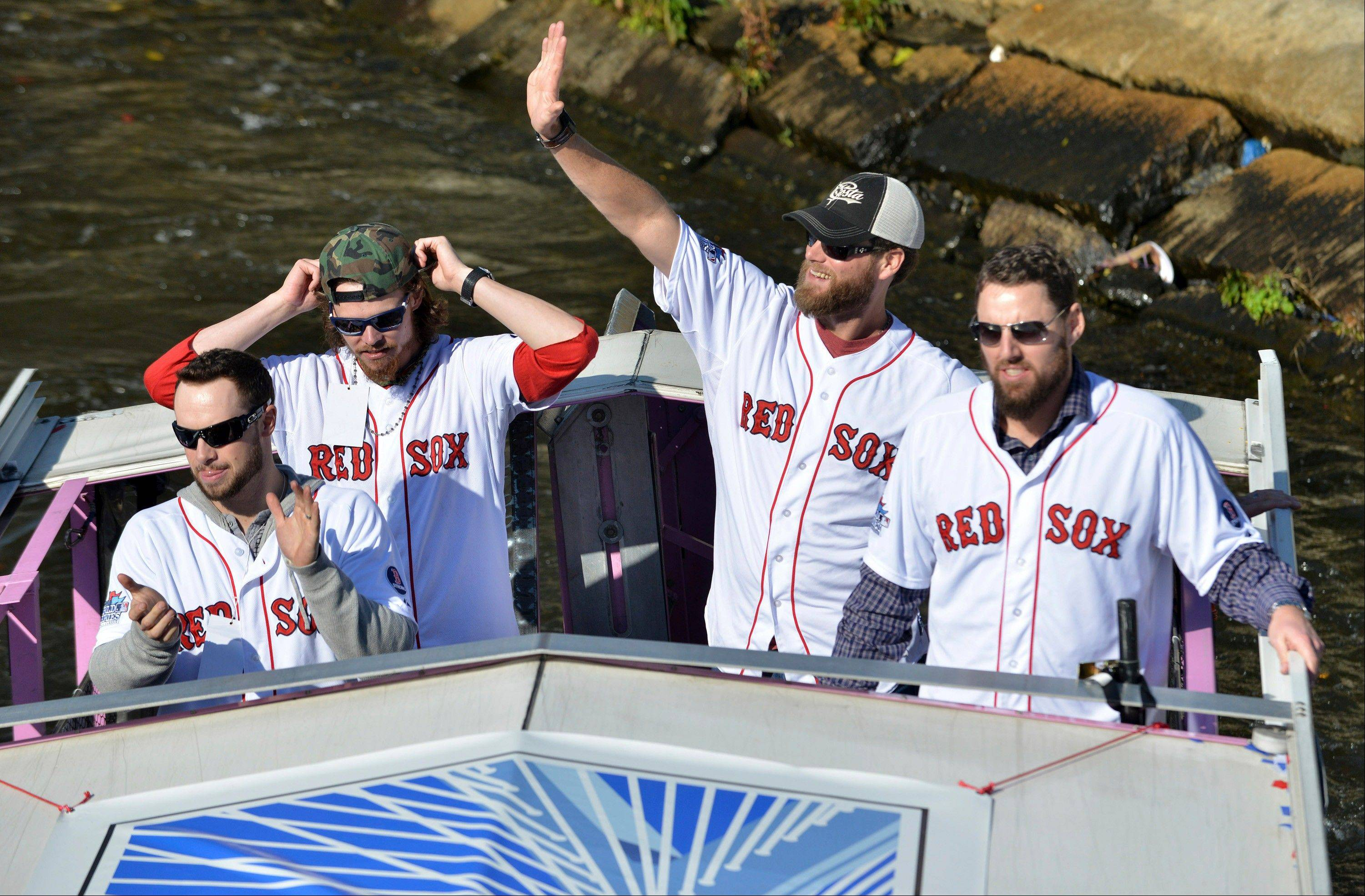 Boston Red Sox players, from left, Daniel Nava, Clay Buccholz, Matt Thornton and John Lackey float along the Charles River in an amphibious duck boat during a victory parade celebrating the team's World Series title Saturday.