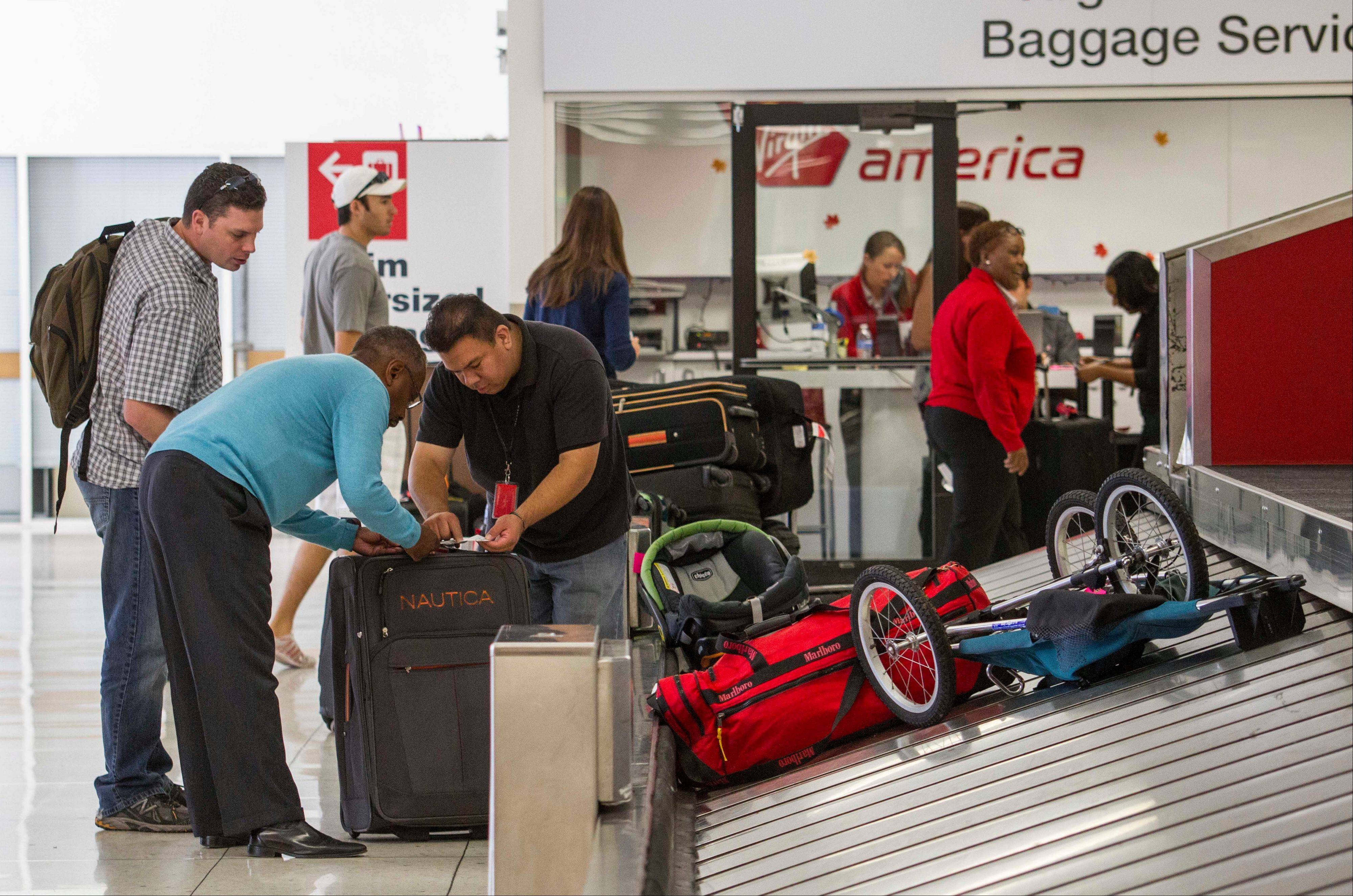 Transportation Security Administration employees help passengers getting back their luggage at Los Angeles International Airport's Terminal 3 on Saturday.