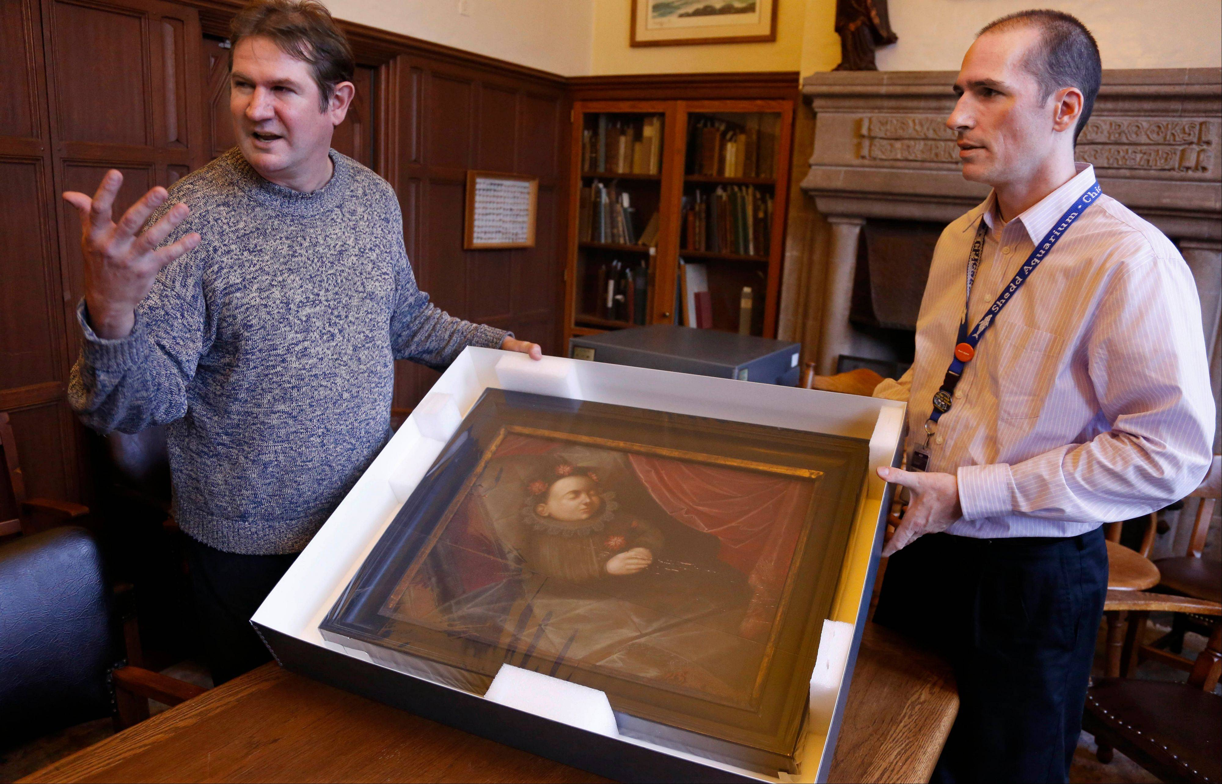 "Scott Krafft, left, curator of the Charles Deering McCormick Library of Special Collections, and manuscript librarian Benn Joseph display a painting of a dead Spanish boy from the 1600s. The portrait is one of the artifacts from the ""Death Collection"" -- an archive of death-related oddities once owned by horror novelist and screenwriter Michael McDowell that have been purchased by Northwestern University."