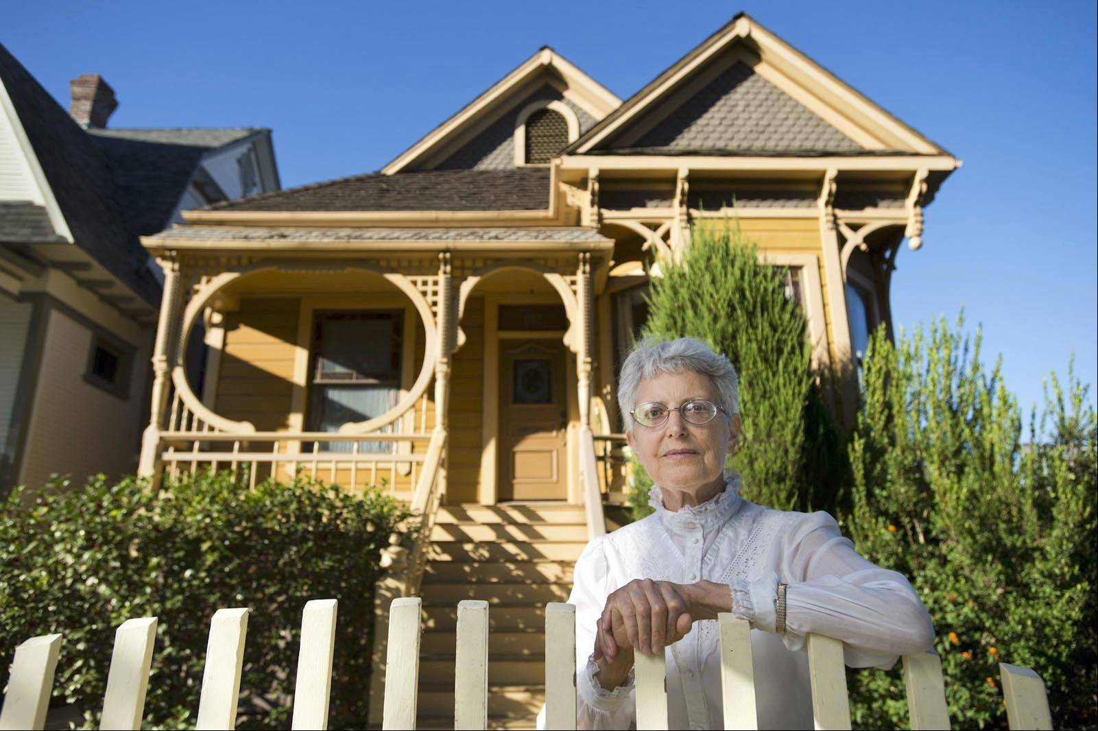Victorian owner Dr. Louise Mehler stands in the front of her 1893 vintage era home.