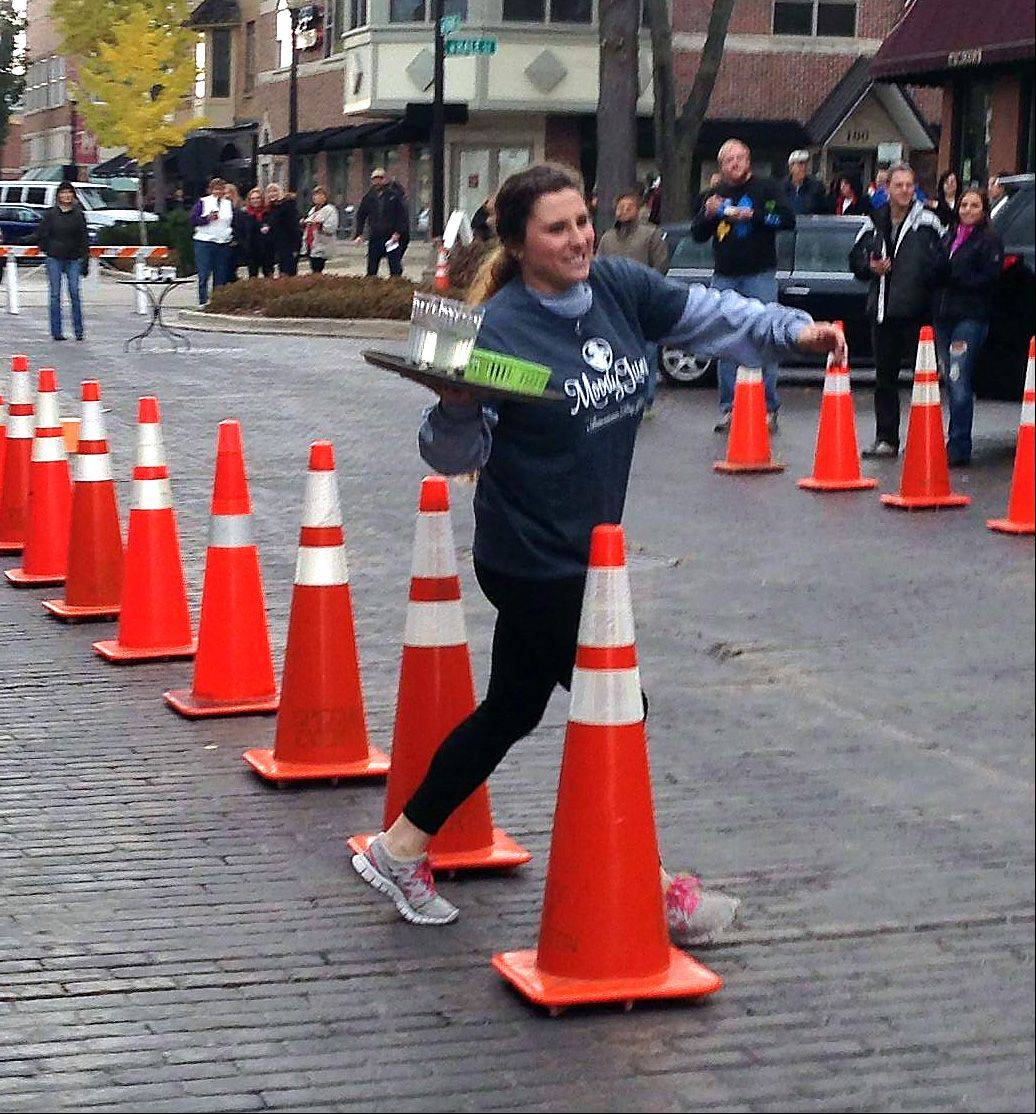 Courtney Windisch, who works at The Bank Restaurant in Wheaton, navigates obstacles in the Waiter Race, part of this year's Chili Cook Off in downtown Wheaton.