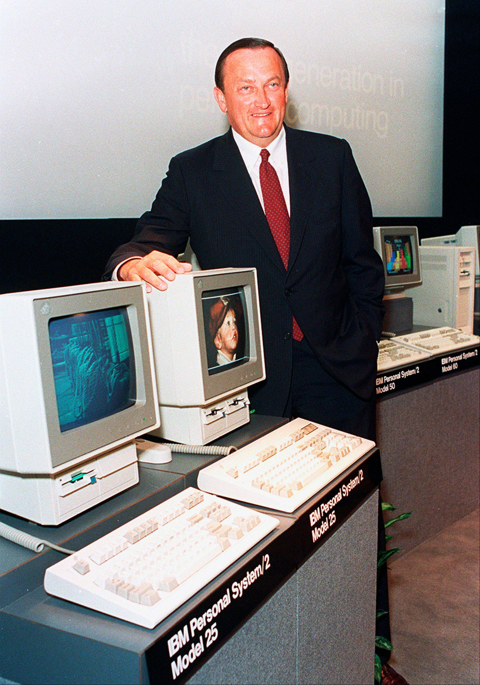 William C. Lowe, a vice president at IBM, poses with two of the company's newest Personal System/2 computers, the model 25, at the unveiling in New York City.